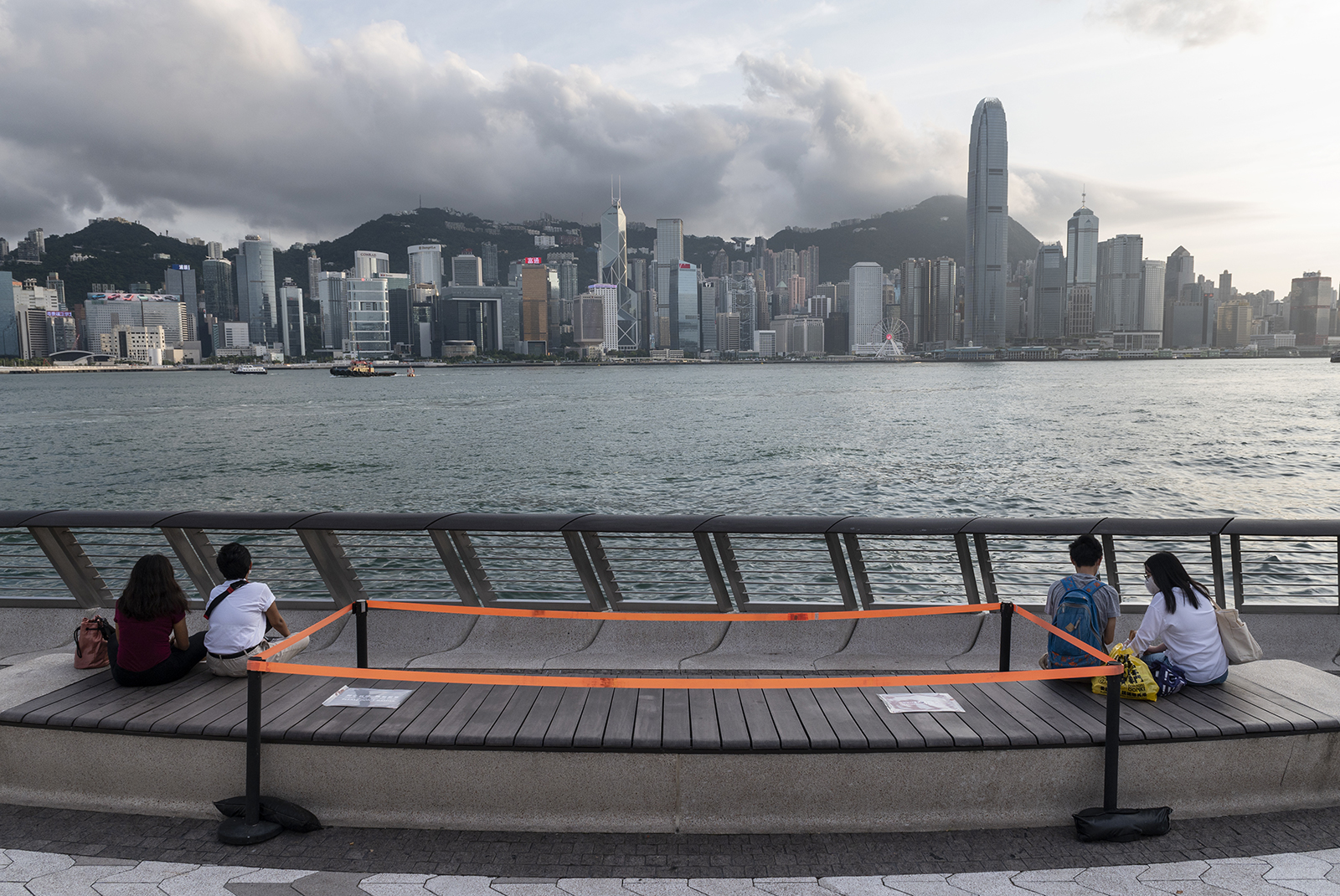 Couples sit and enjoy the view of he Victoria harbor as public benches are seen with orange tape to block access to them in Tsim Sha Tsui, Hong Kong, China, on August 24.
