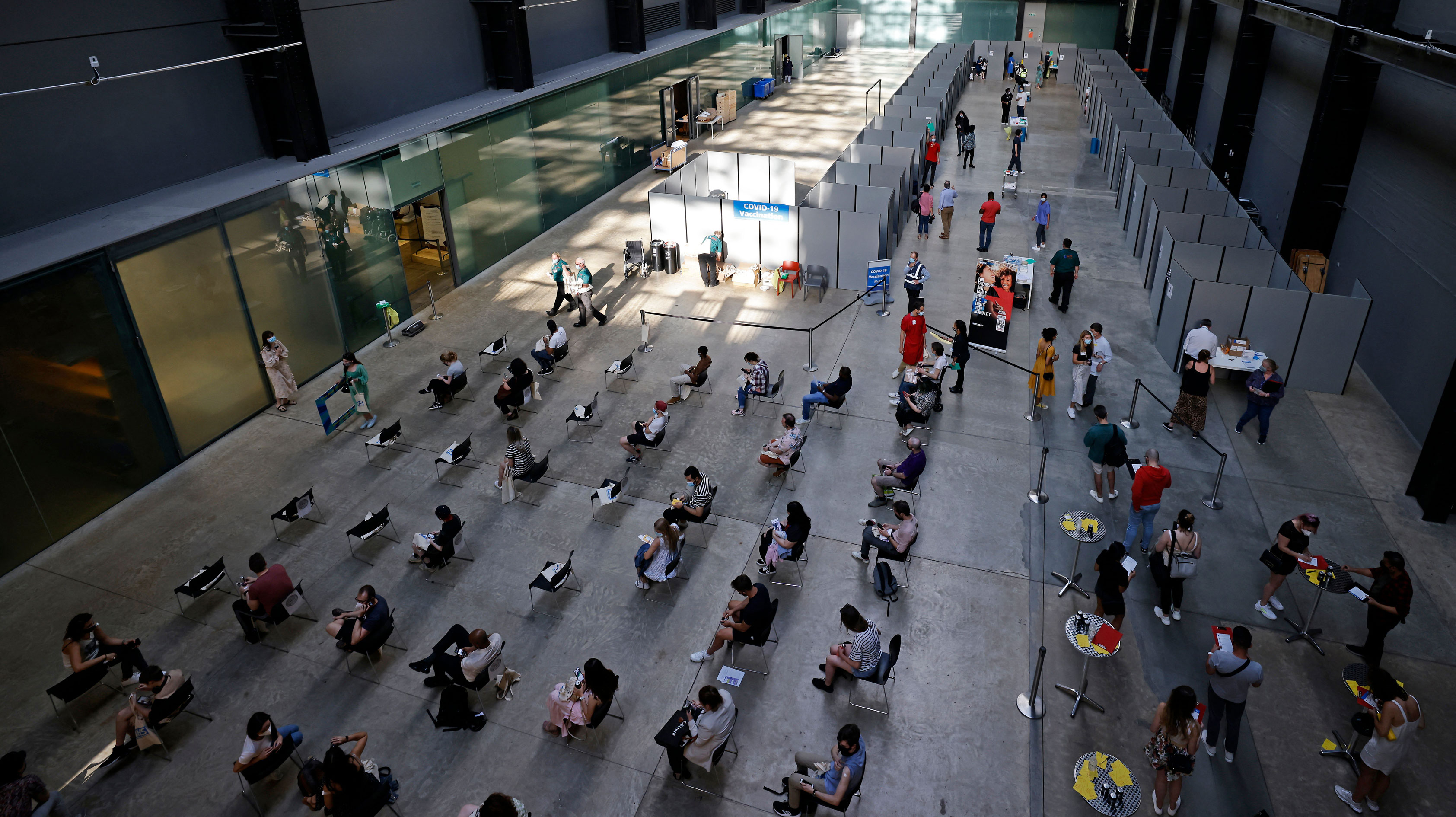 People wait on socially distanced chairs to receive the Pfizer-BioNTech Covid-19 vaccine at a temporary vaccination center at the Tate Modern in central London on Friday, July 16.