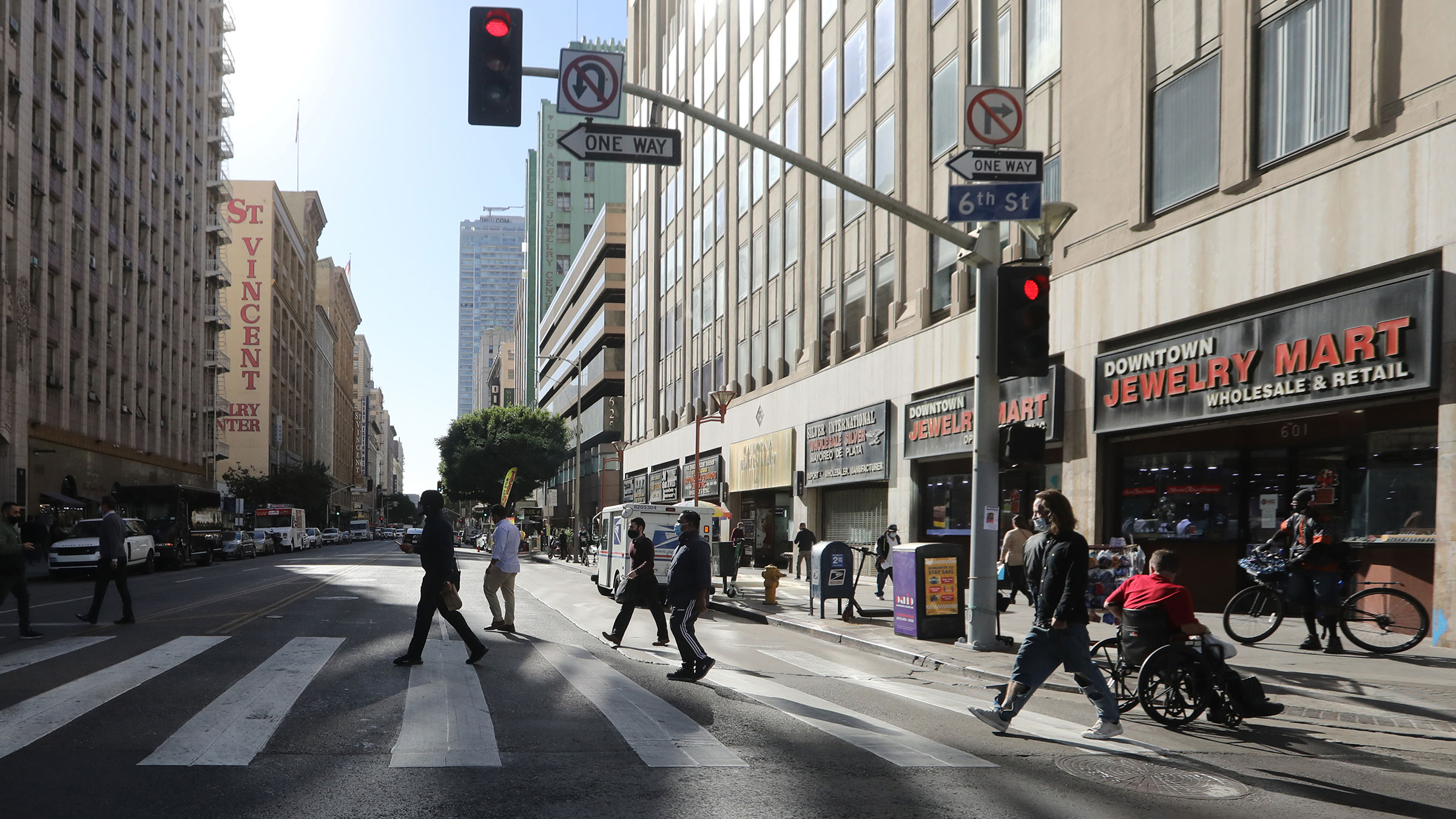 Pedestrians cross a street in downtown Los Angeles, on Thursday, December 3.