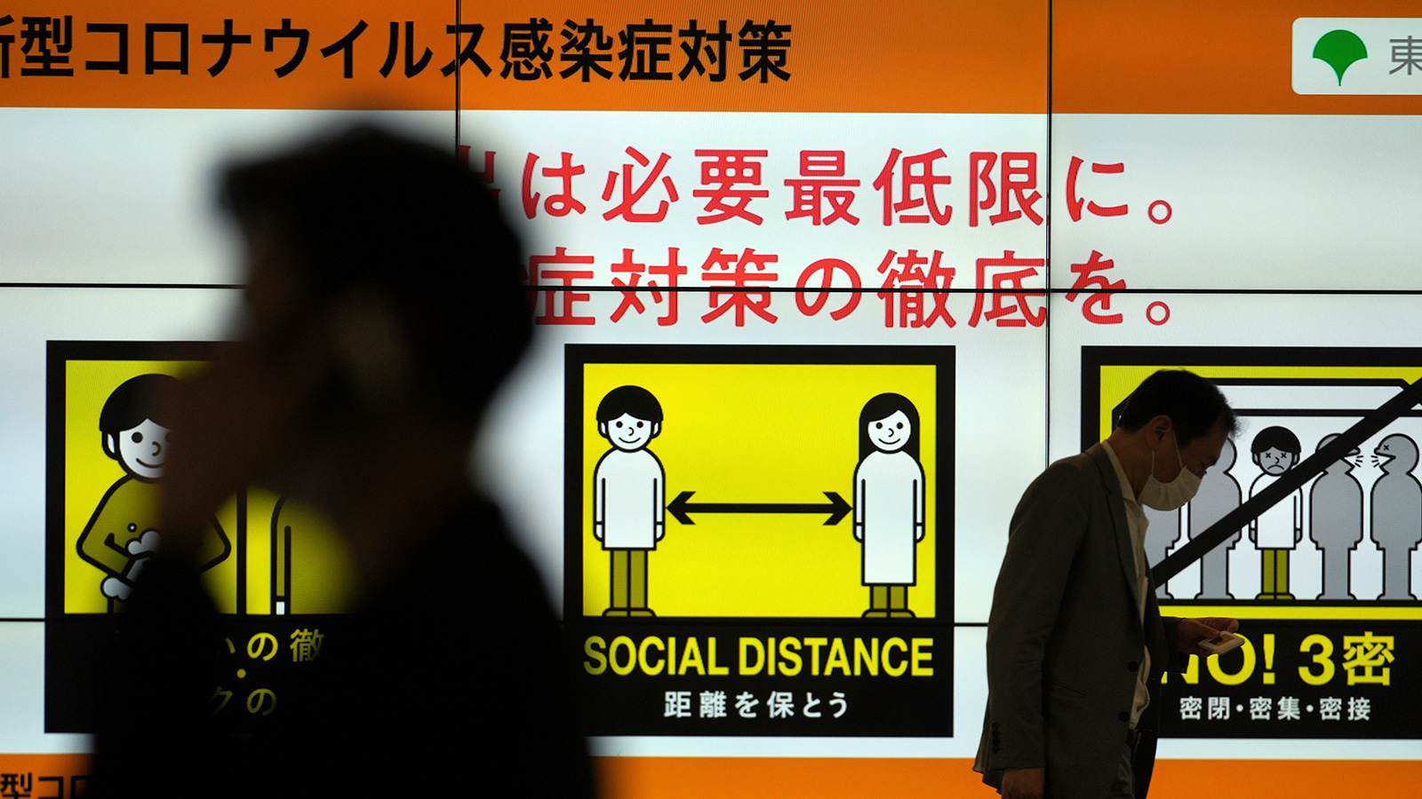 People walk past a public awareness sign for social distancing to help reduce the spread of the coronavirus Tuesday, June 22, in Tokyo.