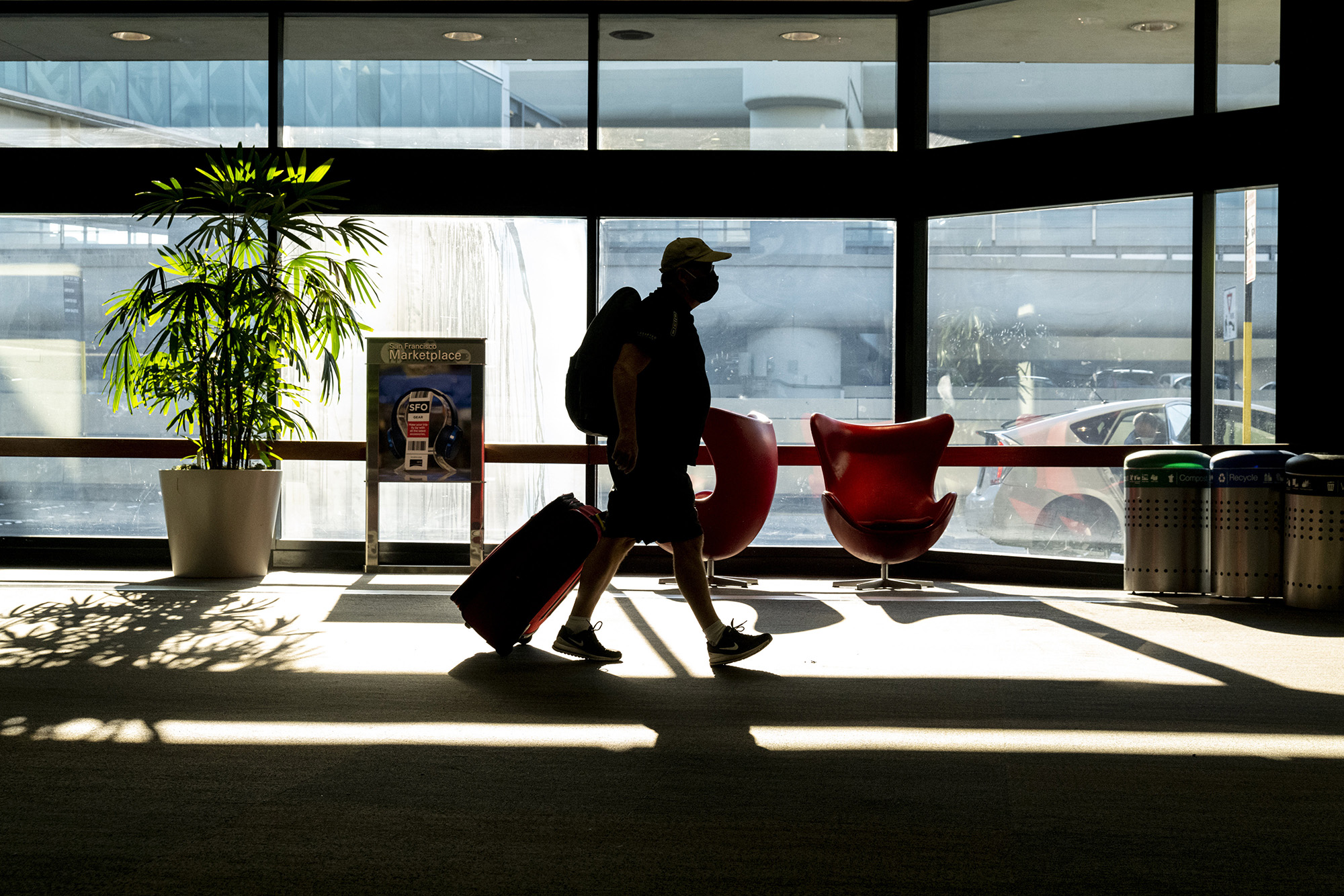 A traveler wearing a protective mask walks in San Francisco International Airport in San Francisco, California, on Monday, Dec. 21, 2020.