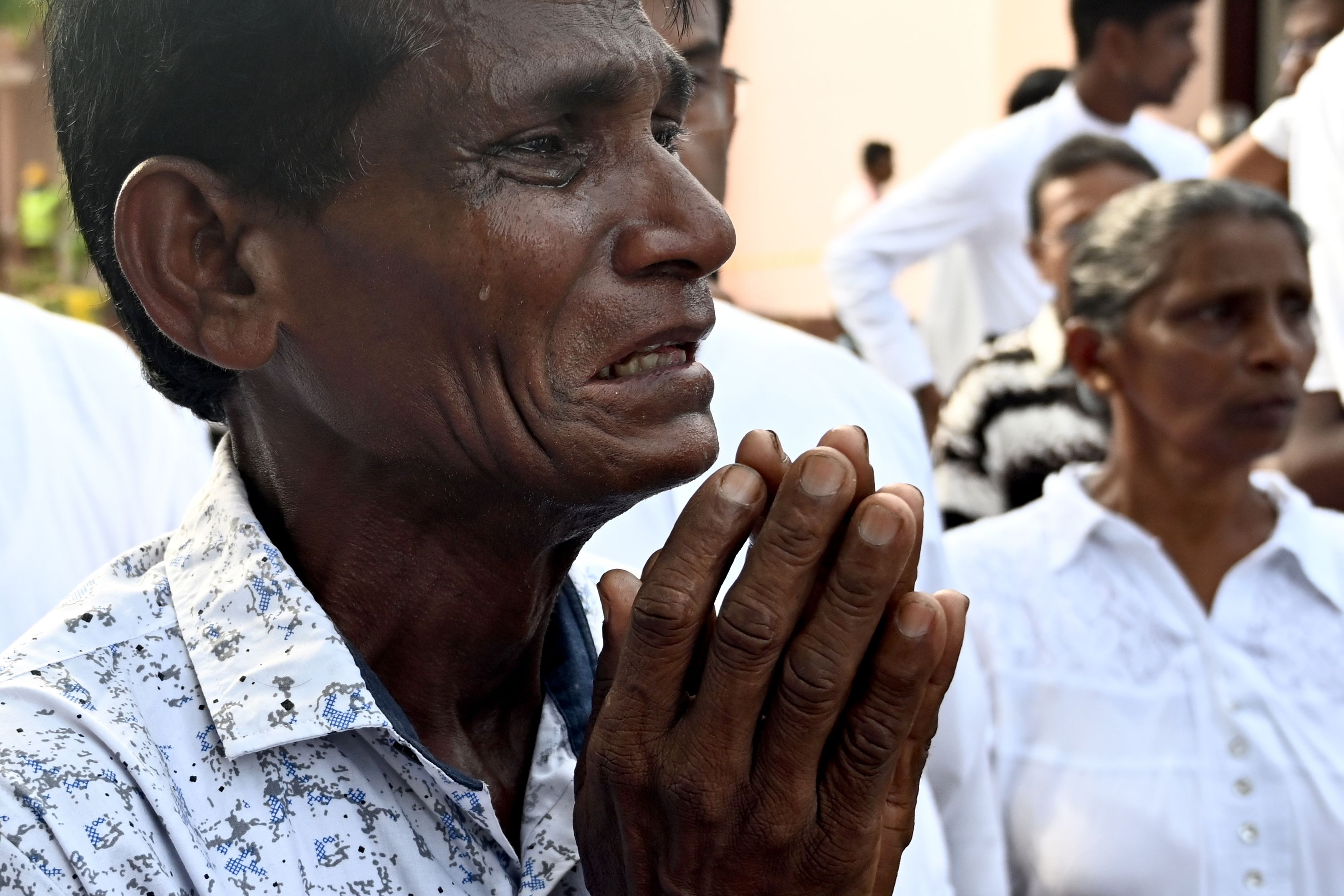 A man cries as he walks behind the coffin of a bomb blast victim after a funeral service at St Sebastian's Church in Negombo.