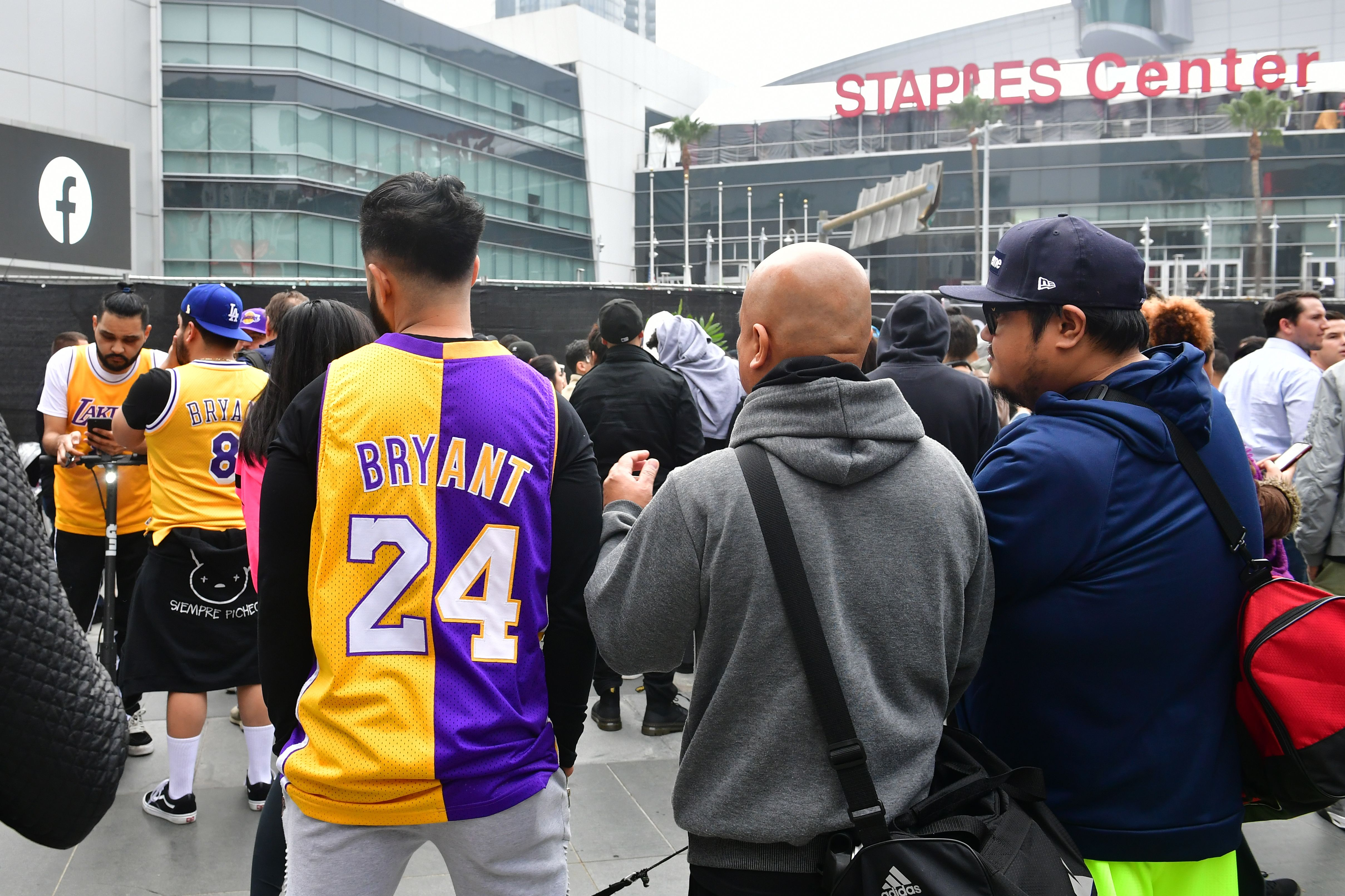 People gather around a makeshift memorial for former Los Angeles Lakers player Kobe Bryant after learning of his death Sunday at LA Live plaza in front of Staples Center in Los Angeles.
