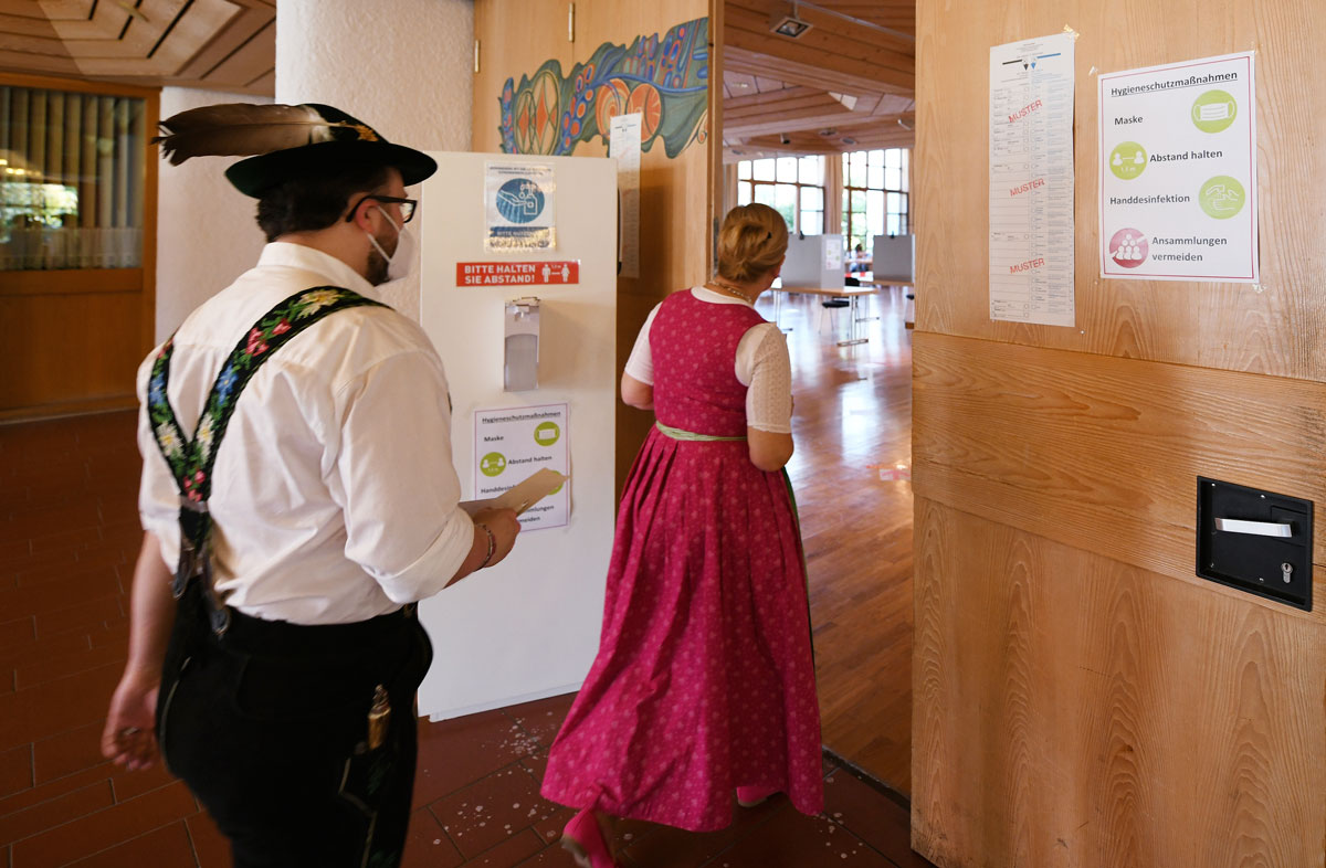 A couple dressed in traditional Bavarian costume arrive at a polling station in Oberammergau, Germany on Sunday, September 26.