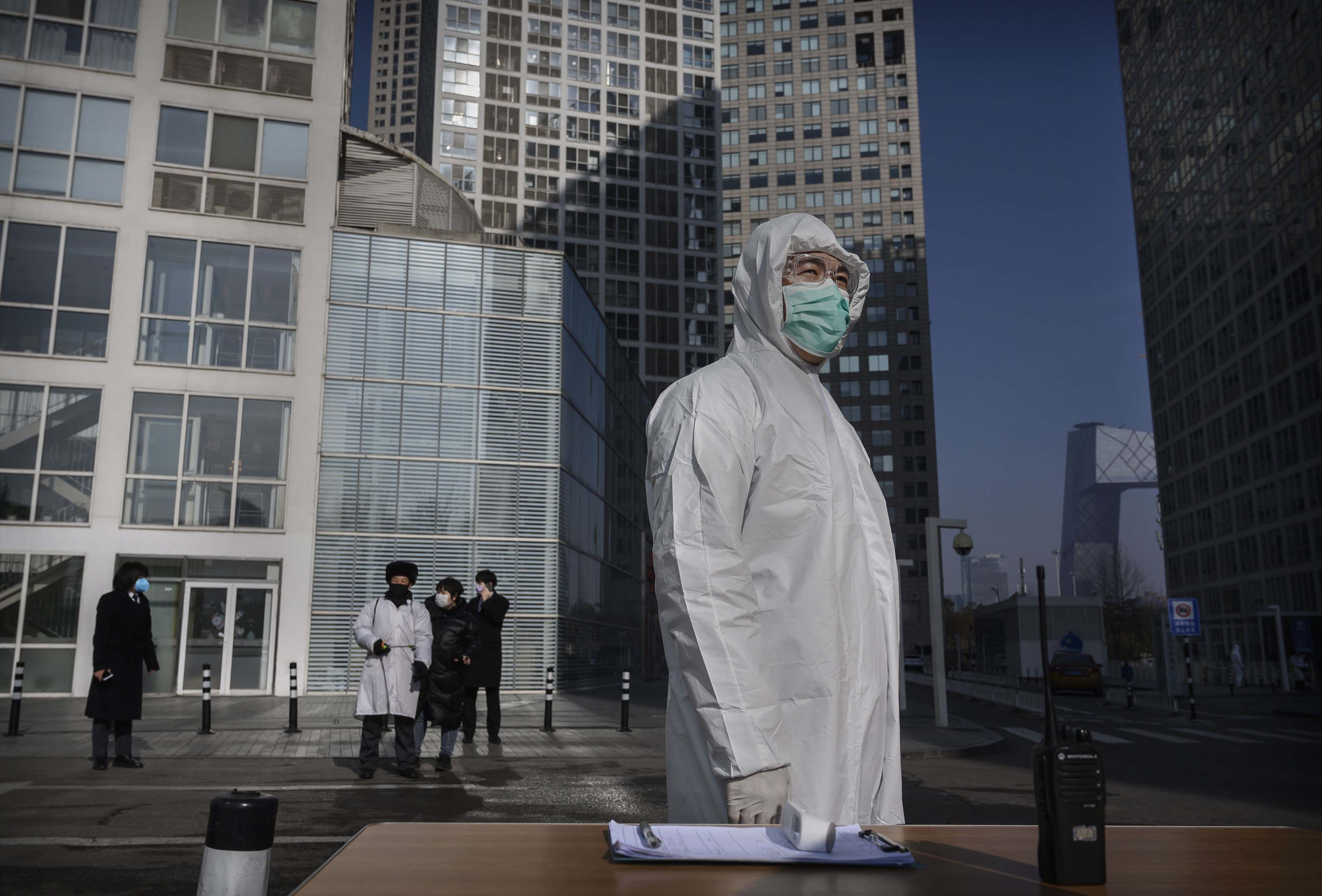 A man wears a protective suit outside an office building in Beijing on Monday, as he waits to screen people returning to work.
