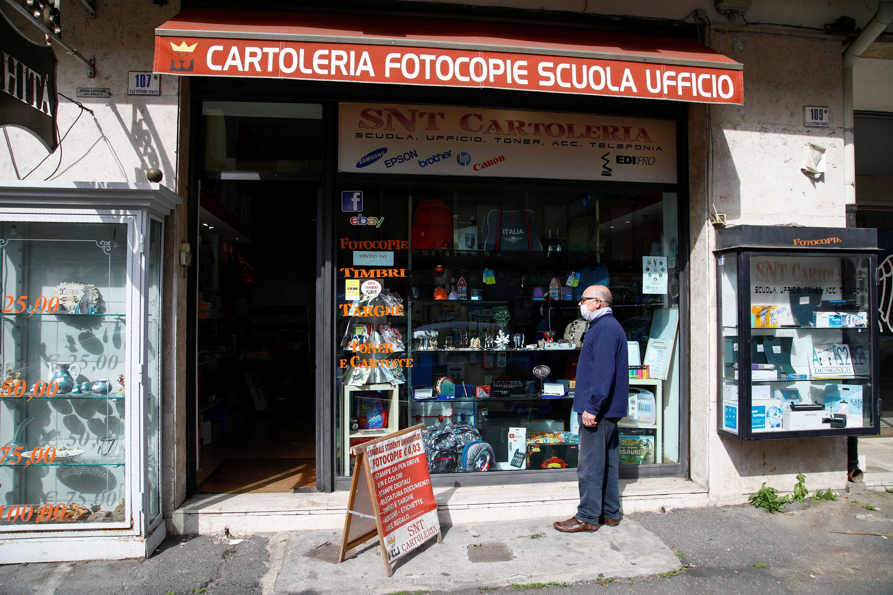 A man stands in front of a store in Catania, Italy, after the Italian government allowed some shops to reopen on April 14.