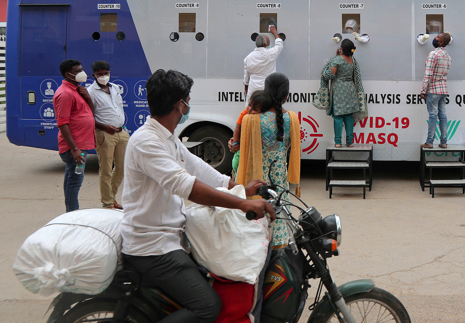 People get their nasal swab samples taken at a mobile testing centre in Hyderabad, India, on July 31.