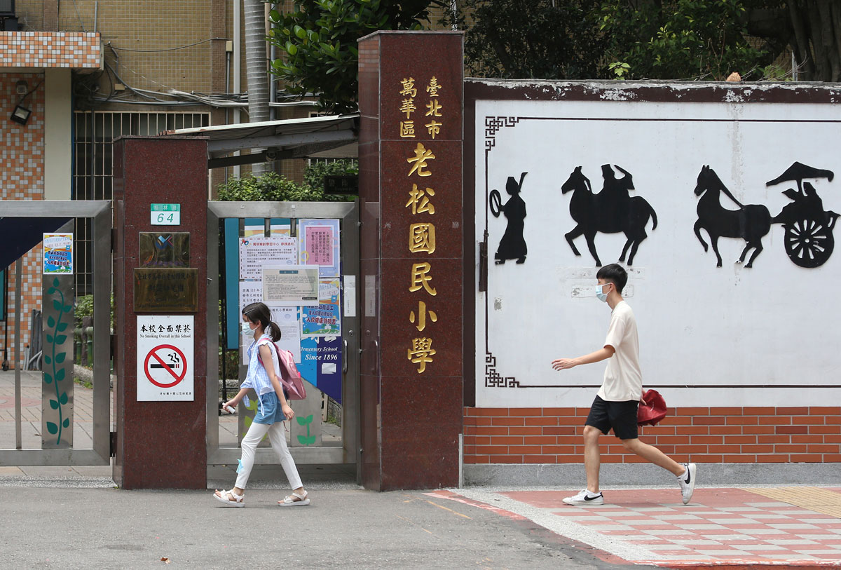 Students wearing face masks walk past a closed primary school in Taipei, Taiwan on May 18.