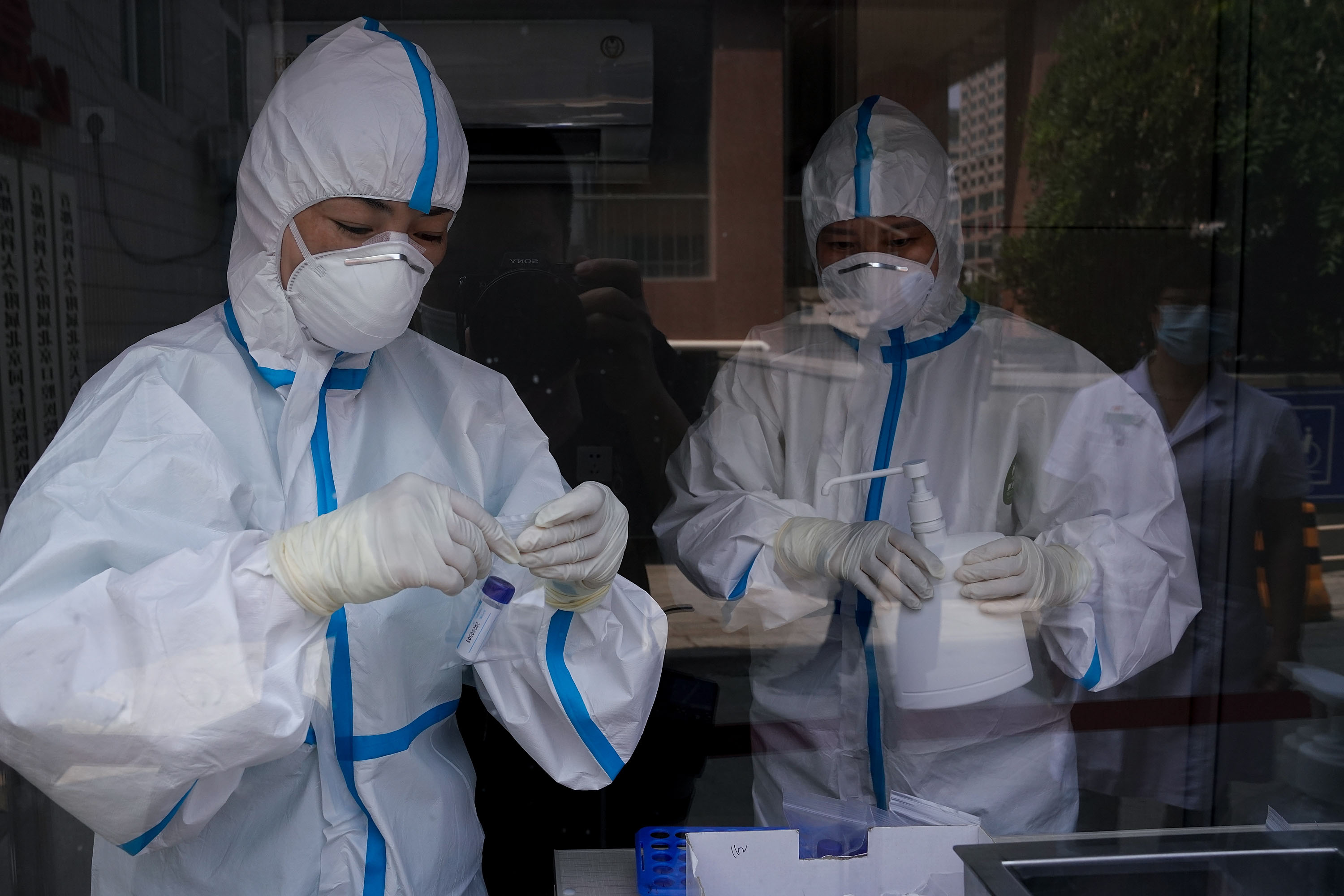 Medical workers check samples at a Beijing hospital testing station on July 14.