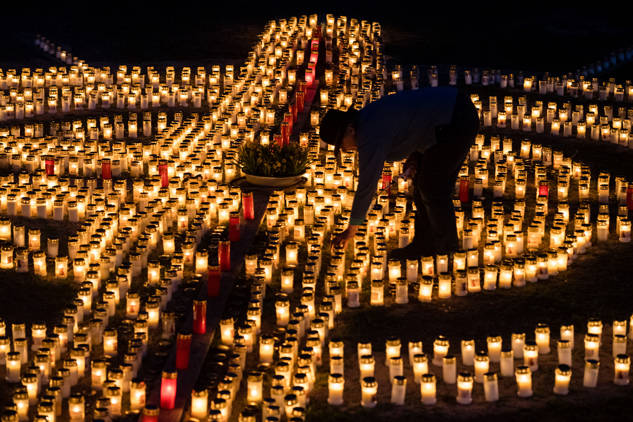 Gertrud Schop, 60, lights candles in the shape of a cross for Germany's deceased victims of Covid-19 on her property in Zella-Mehlis, Germany, on April 17.