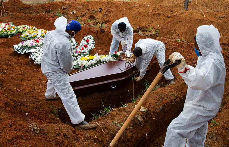 Cemetery workers in protective suits bury a victim of coronavirus at the Vila Formosa cemetery on Thursday, July 16, in Sao Paulo, Brazil.