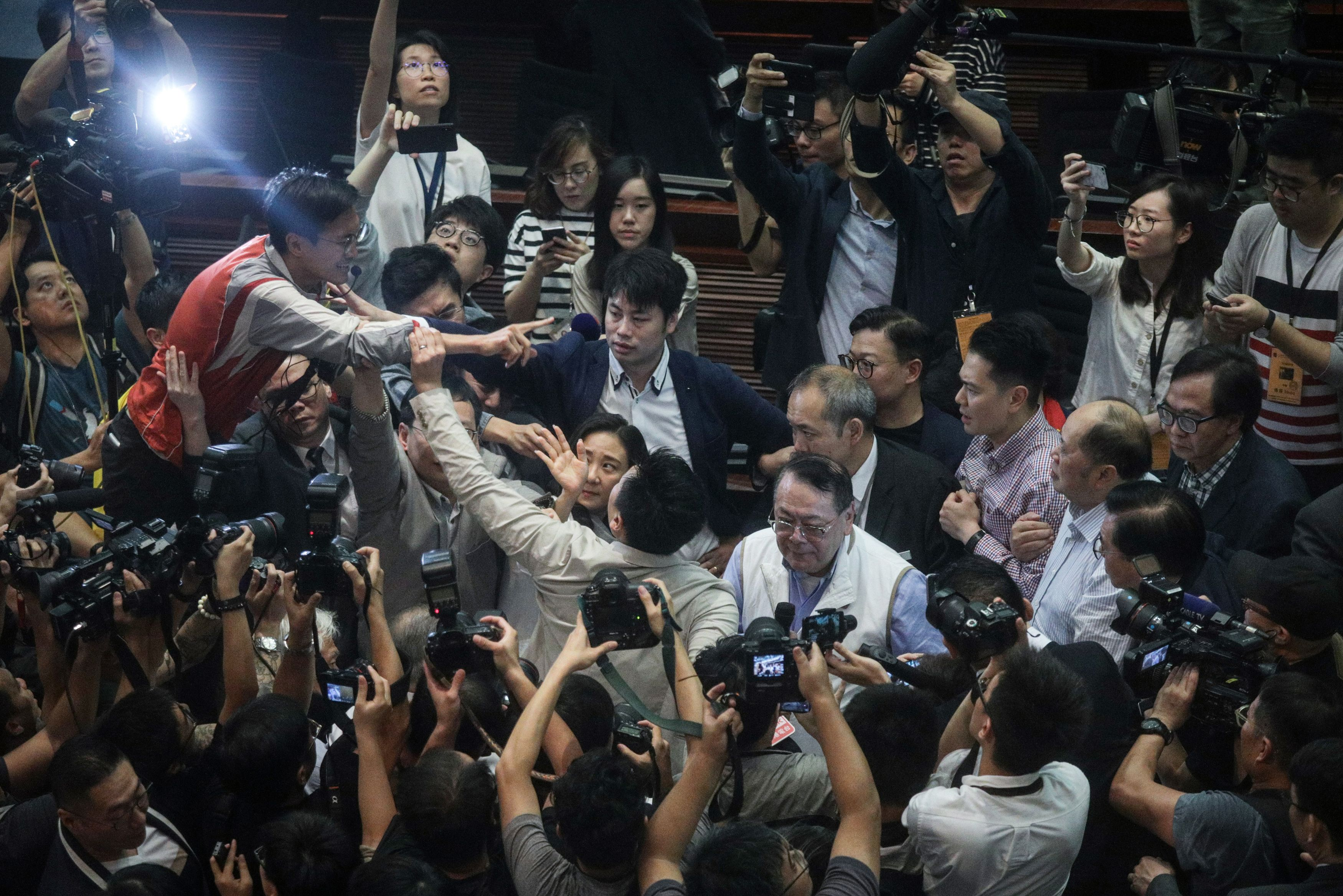 Hong Kong pro-Beijing lawmaker Abraham Shek (centre right in white vest) is escorted from a legislative meeting after scuffles broke out between pro-Beijing and pro-democracy lawmakers over the proposed extradition law in the Legislative Council in Hong Kong on May 11, 2019.