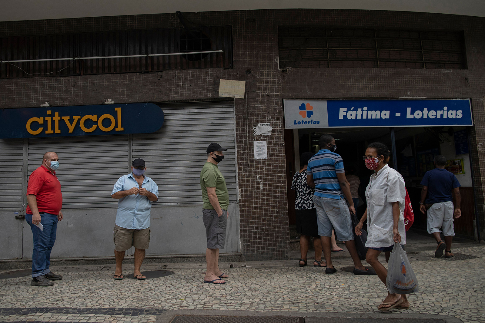 People are seen on a queue to access a lottery shop at the Lapa neighborhood during the Covid-19 pandemic in Rio de Janeiro, on April 8.