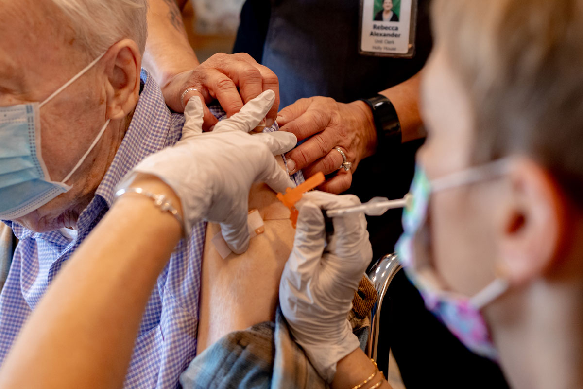 A healthcare worker administers a third dose of the Pfizer-BioNTech Covid-19 vaccine at a senior living facility in Worcester, Pennsylvania on August 25.