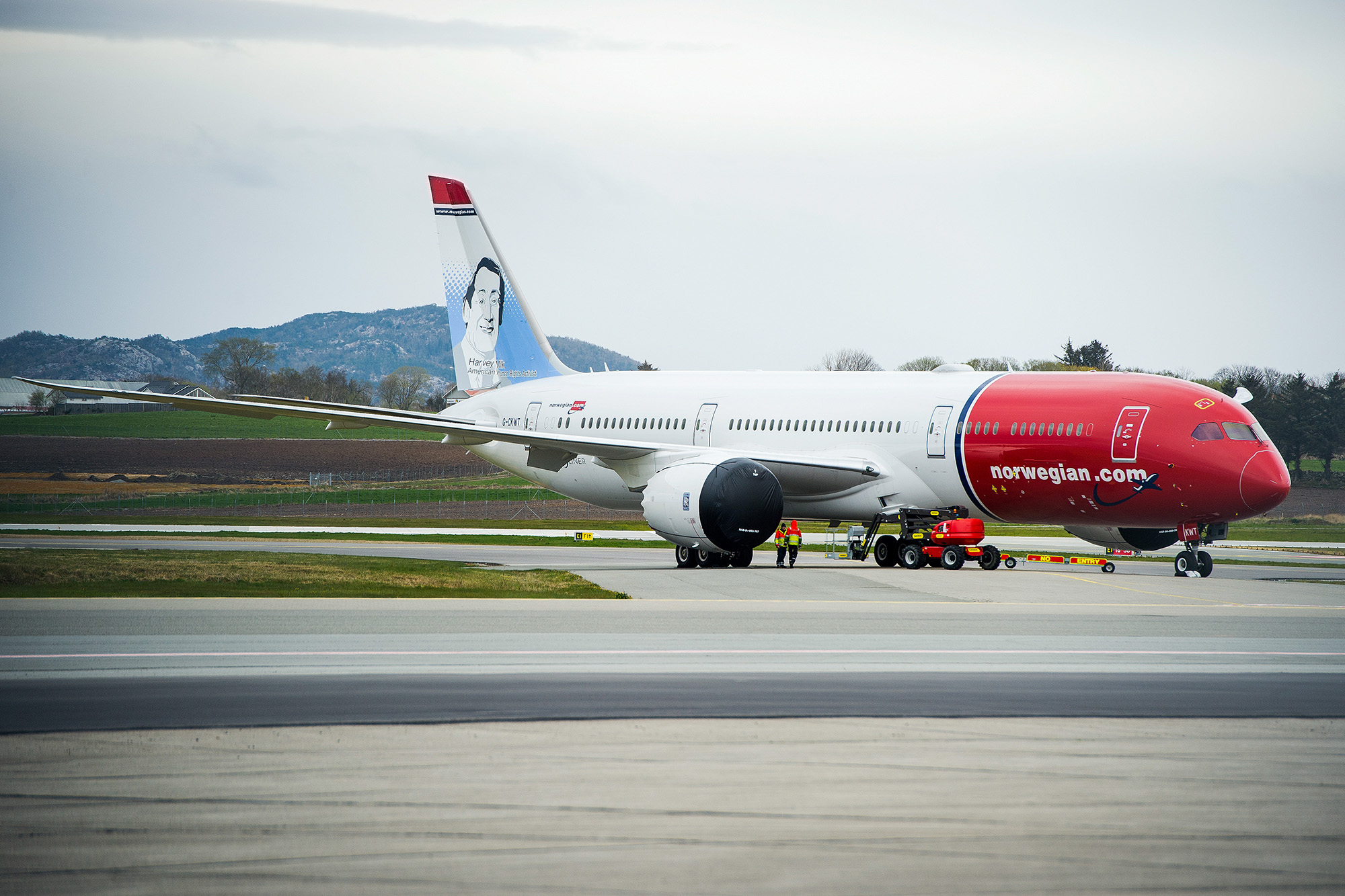 Workers wearing high-visibility jackets stand near a passenger aircraft, operated by Norwegian Air Shuttle ASA, grounded at Stavanger Airport in Stavanger, Norway, on April 30.