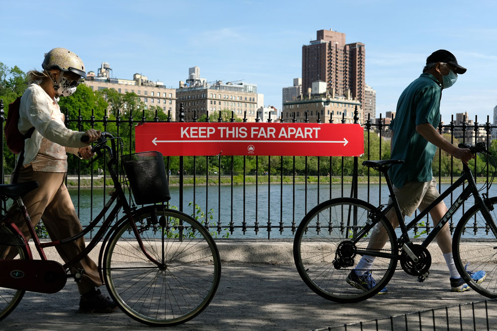 People wearing protective masks walk their bicycles past a social distancing sign at Jacqueline Kennedy Onassis Reservoir in Central Park during the coronavirus pandemic on May 17 in New York City.