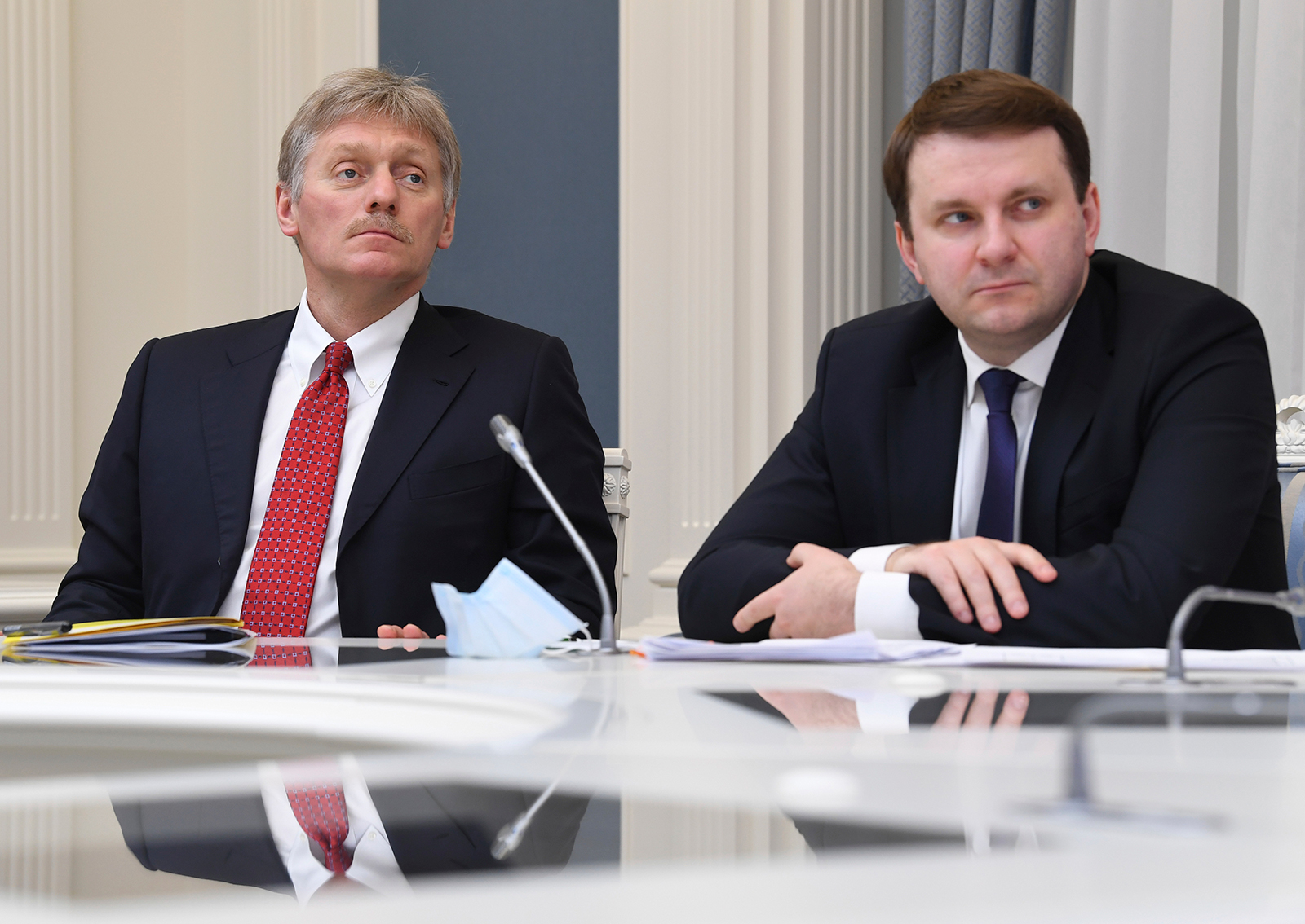 Kremlin spokesman Dmitry Peskov, left, and Russian Presidential Aide Maxim Oreshkin attend a meeting with President Vladimir Putin on economic issues via teleconference call in Moscow, on Tuesday, April 14.