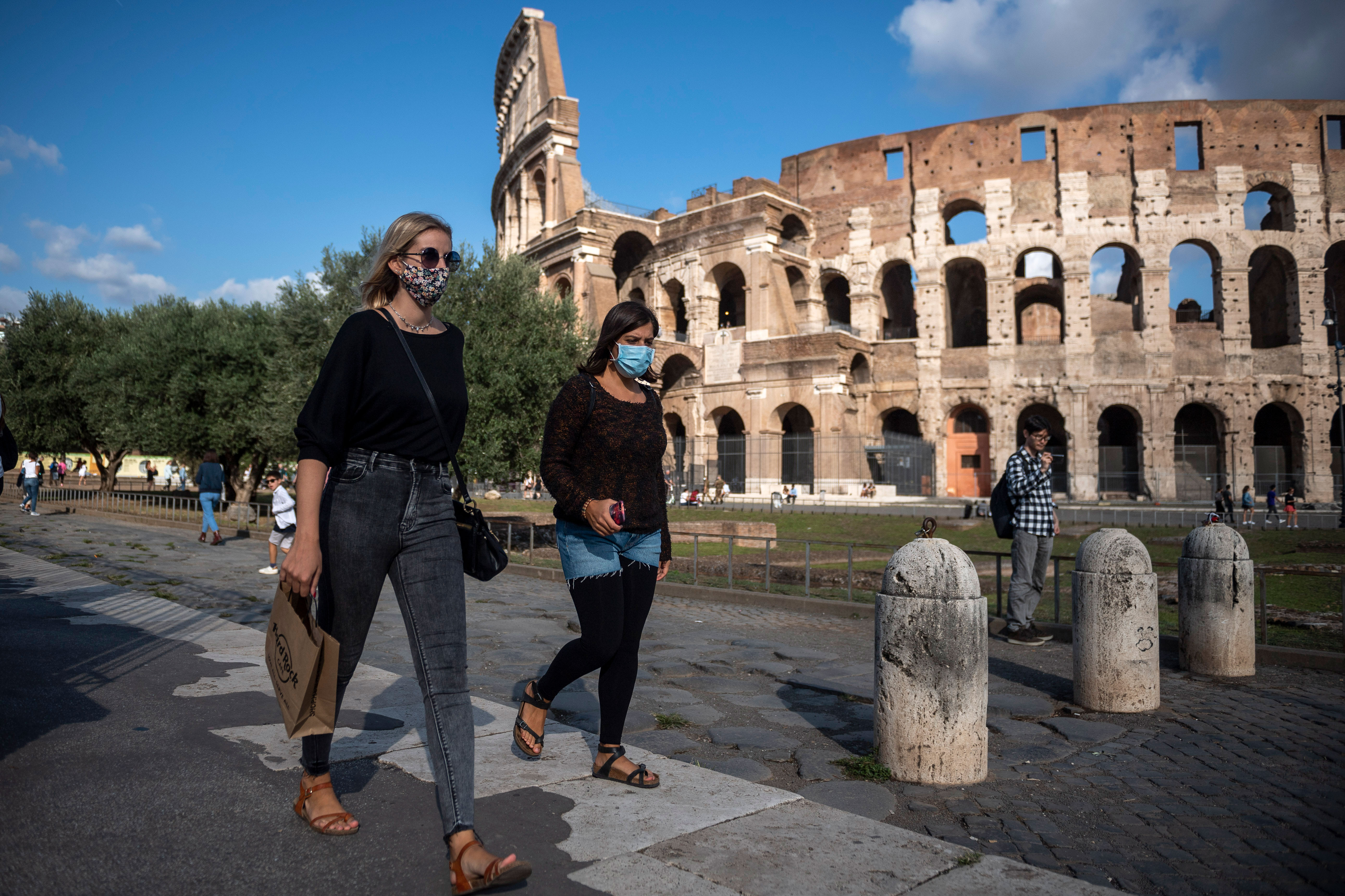 People walk by the Colosseum in Rome on October 1.