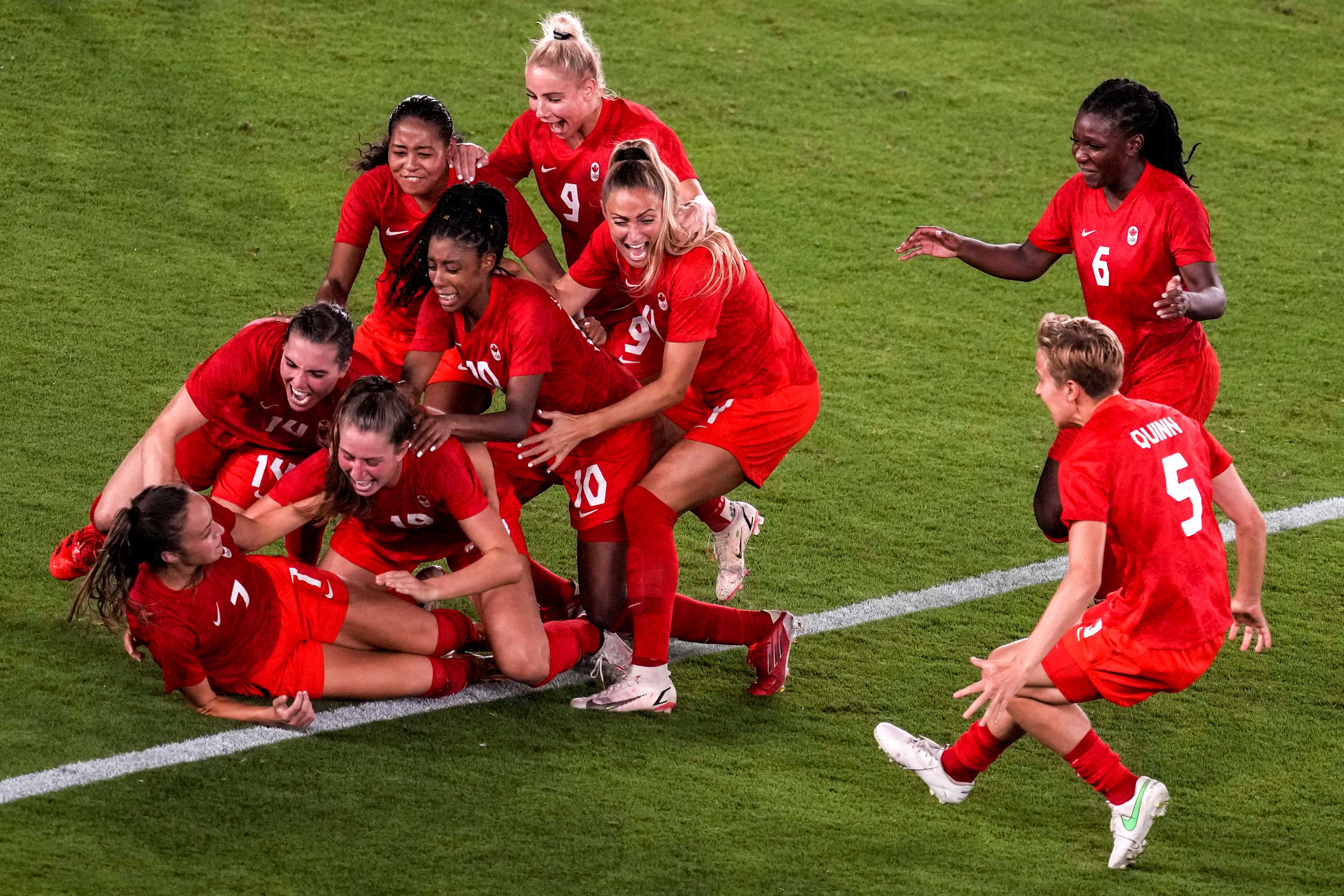 Teammates celebrate with Canada's Julia Grosso after she scored the winning goal against Sweden in the gold medal football final on August 6.
