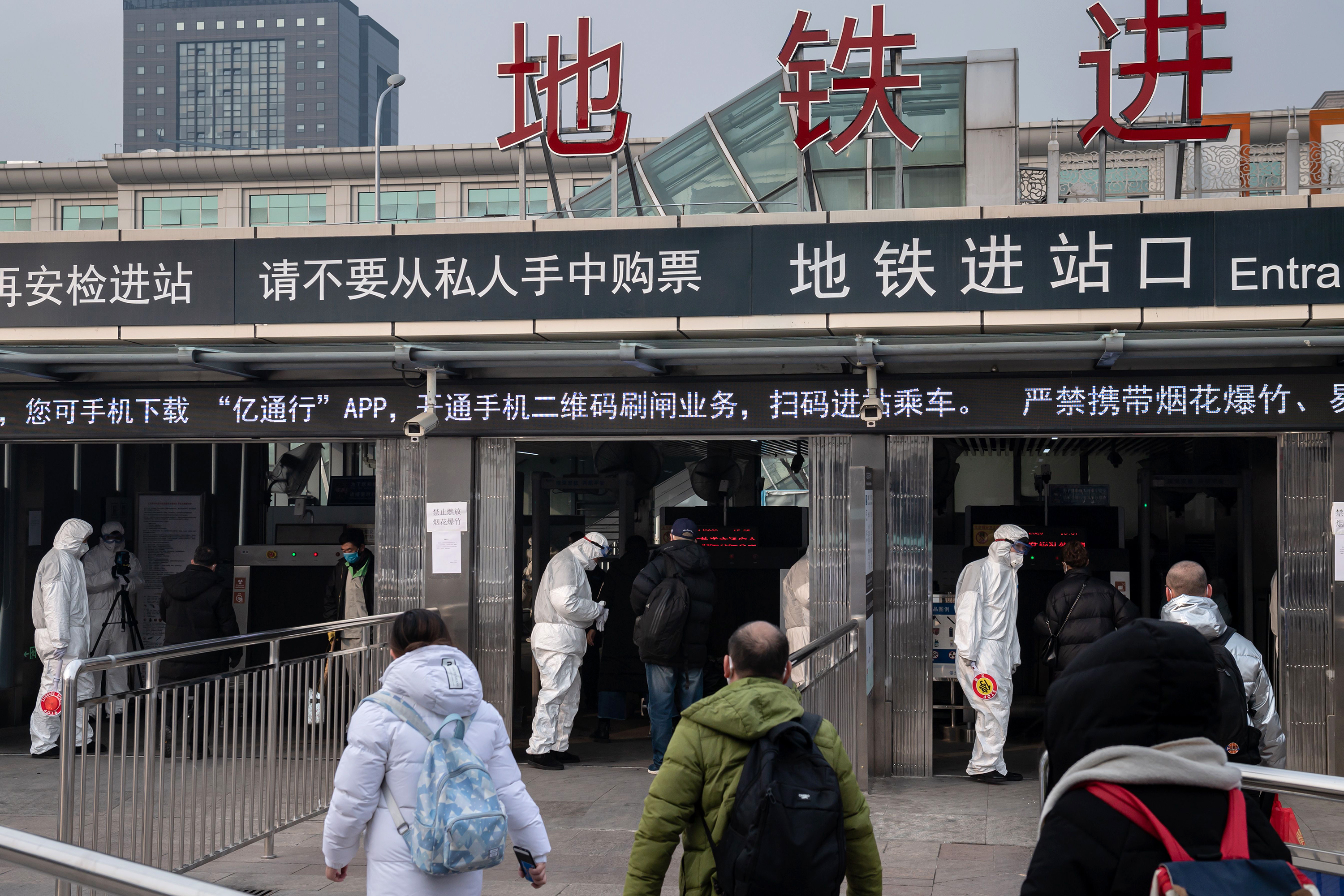 Security personnel wearing protective clothing check the temperature of people using portable devices and an advanced thermo camera (L) at a subway station entrance in Beijing on January 27.