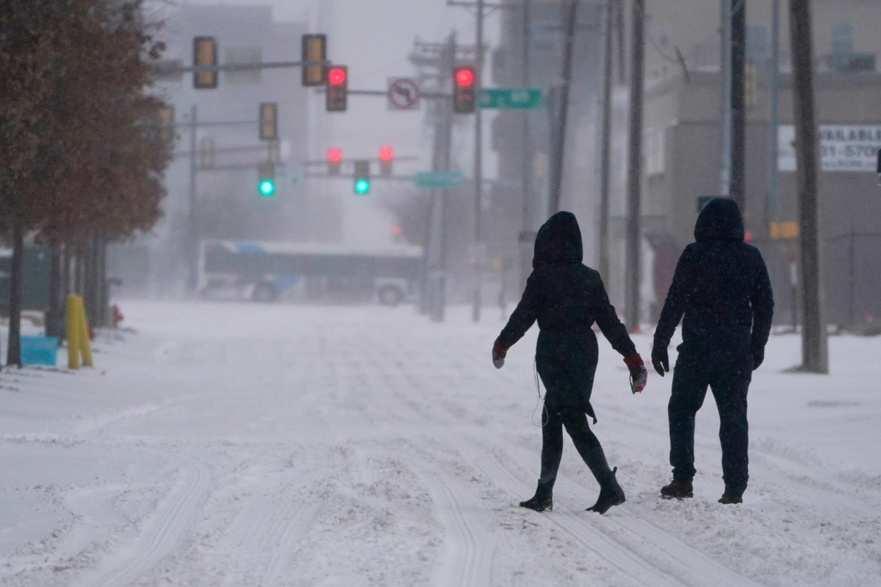 People walk down a street during a winter storm in Oklahoma City, Sunday, February 14.