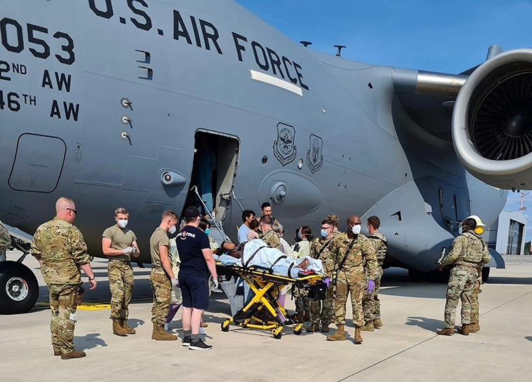 Medical support personnel help an Afghan mother, whose identity has been digitally obscured at source, with her family off a U.S. Air Force C-17 transport aircraft moments after she delivered a child aboard the aircraft upon landing at Ramstein Air Base, Germany, on August 21.