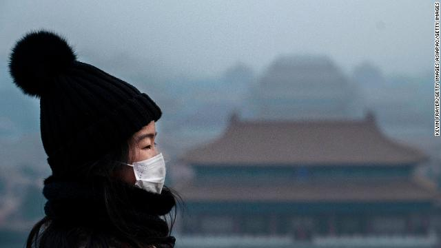 A Chinese girl wears a protective mask as she stands looking towards the Forbidden City, which was closed by authorities, in Beijing.