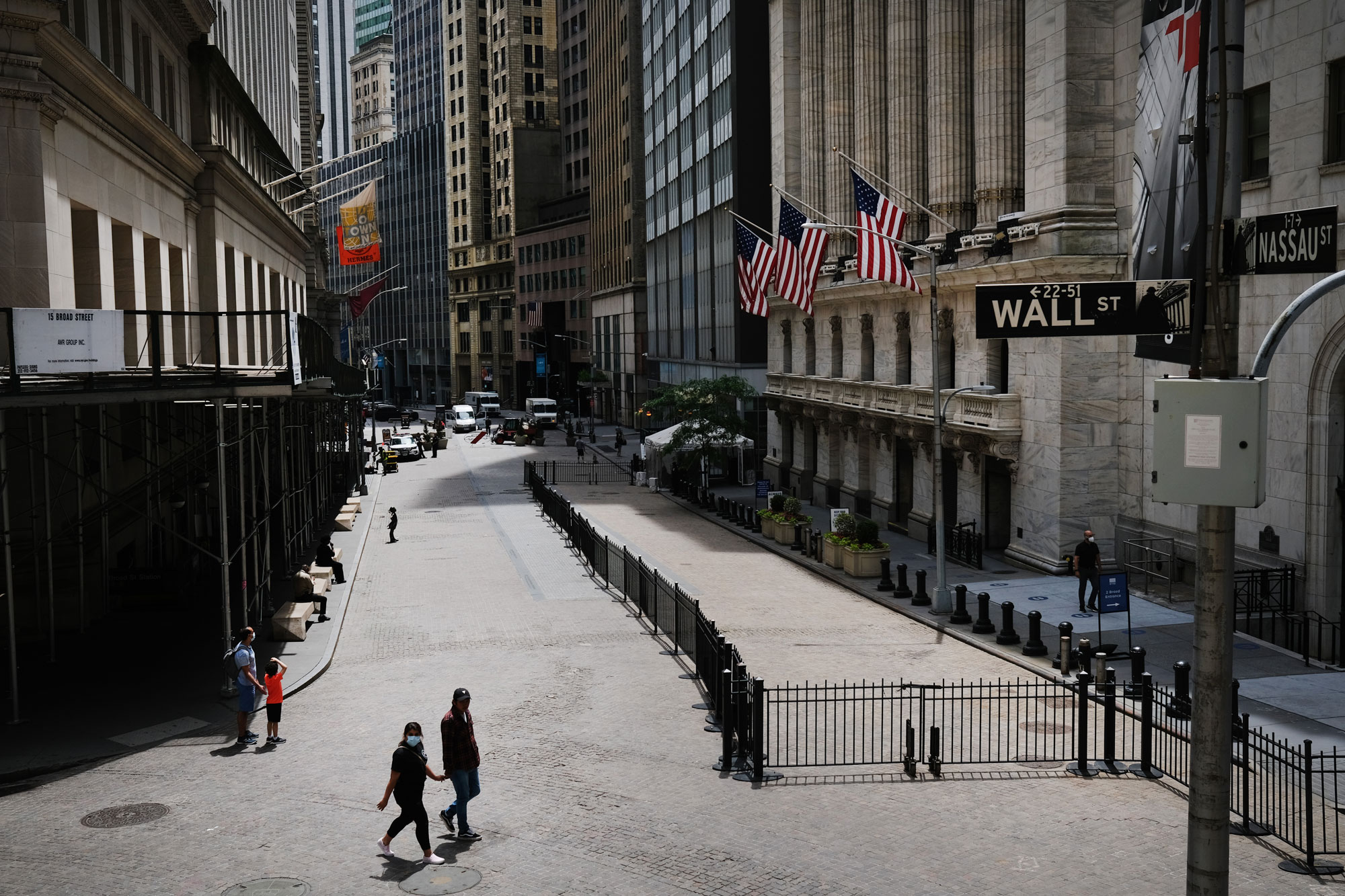 People walk by the New York Stock Exchange in an empty Financial District on June 15 in New York.