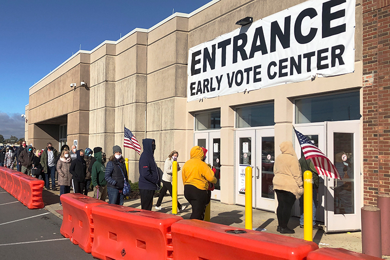 People bundled against the cold stand in a slowly moving line to cast early votes at the Franklin County Board of Elections on Friday, Oct. 30, 2020, in Columbus, Ohio.