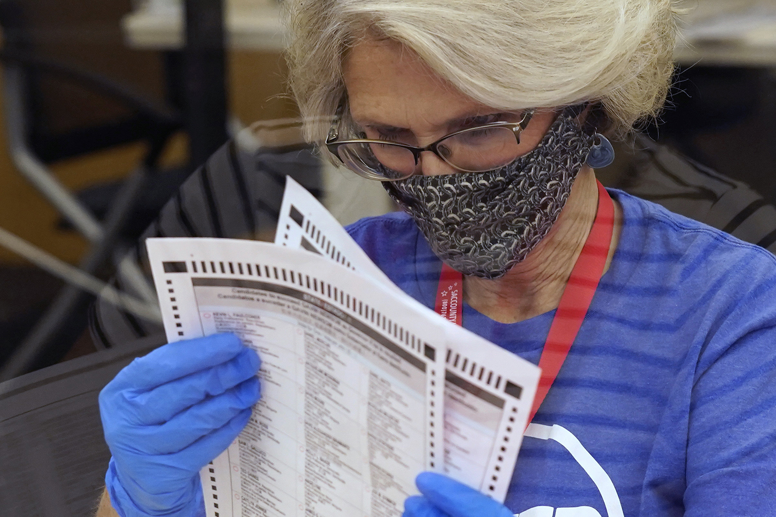 Gerri Kanelos inspects a ballot for damage before they are sent to be tabulated at the Sacramento County Registrar of Voters Office in Sacramento, California on Tuesday, September 14.