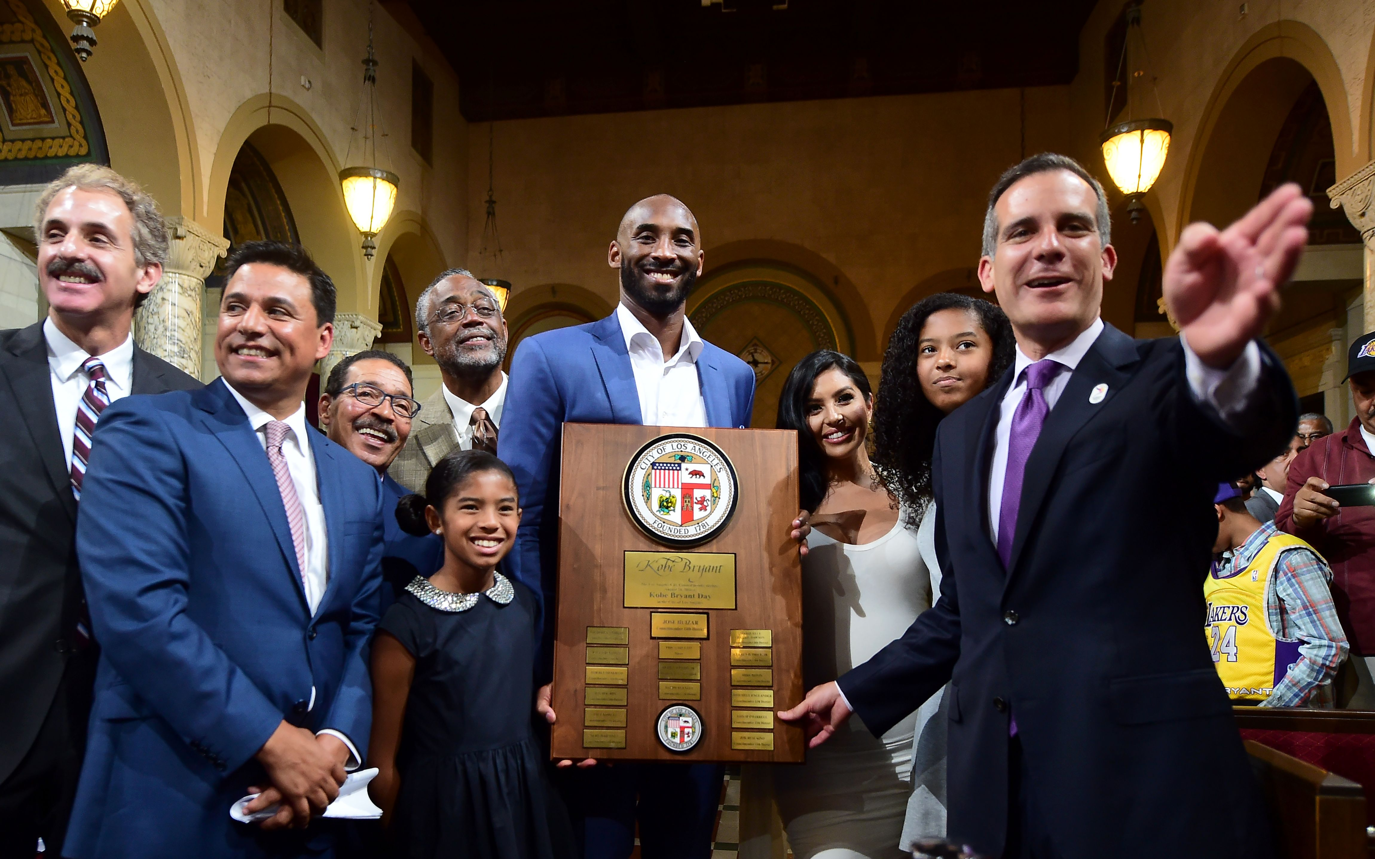 Los Angeles Mayor Eric Garcetti, right, gestures while posing with Kobe Bryant and his family after Bryant was honored at a city council meeting with Kobe Bryant Day on August 24, 2016.