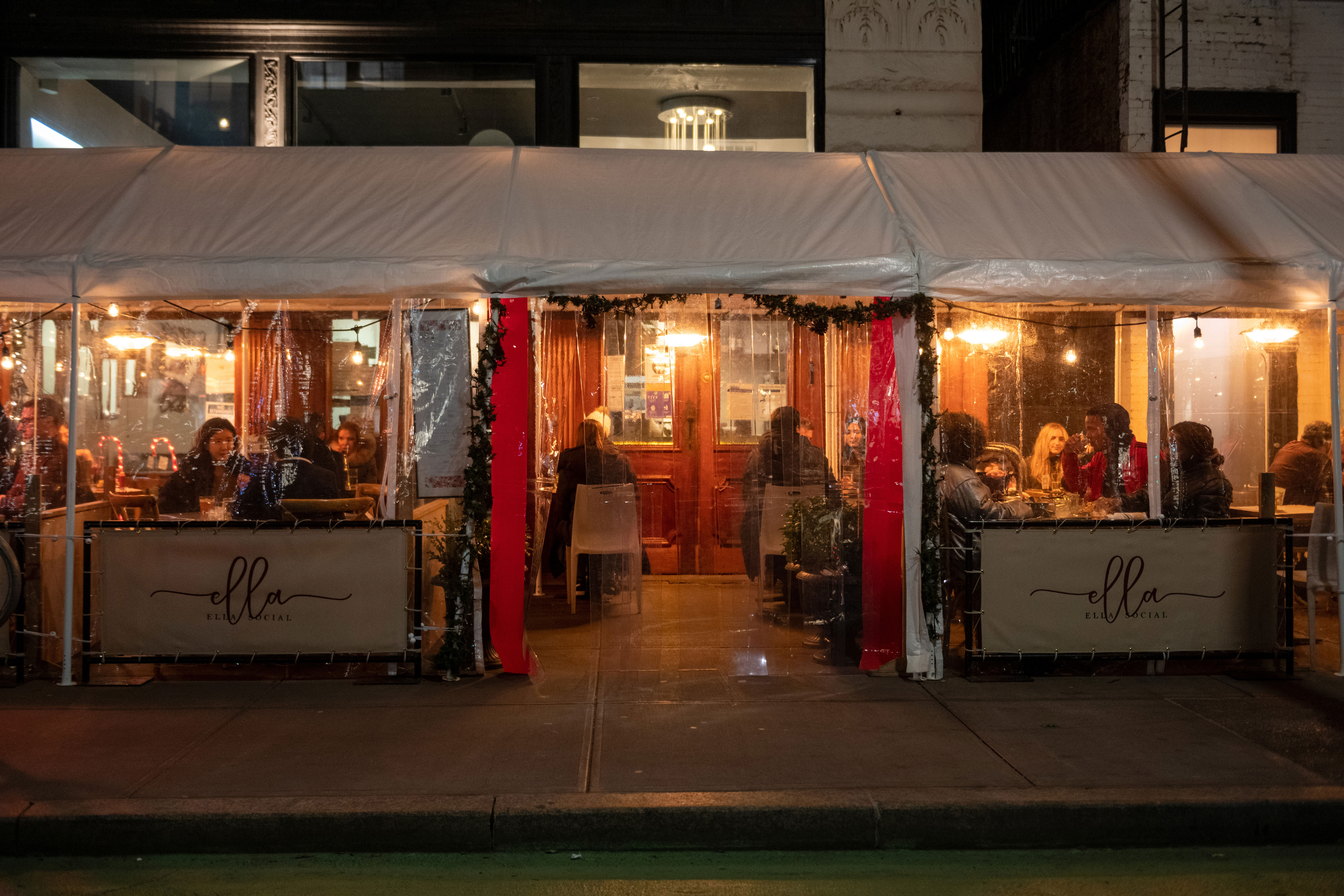 People dine outdoors under a plastic tent at a restaurant on the Upper West Side in New York on December 30, 2020.