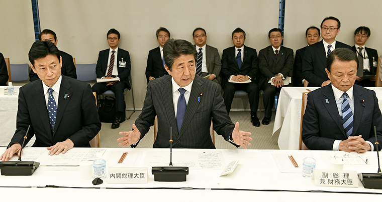 Japanese Prime Minister Shinzo Abe, center, speaks during a meeting on the coronavirus crisis on March 20, in Tokyo.