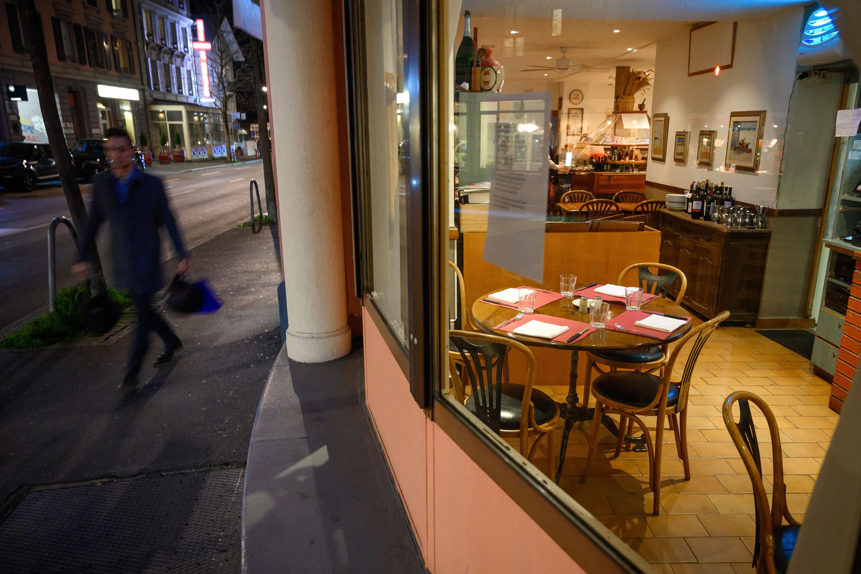 A man walks past an empty restaurant in Lausanne, Switzerland, on March 13.