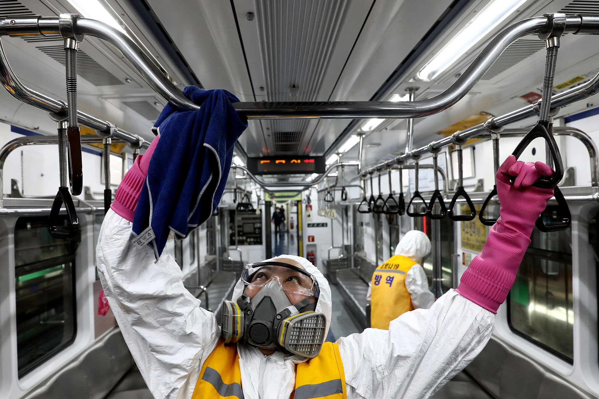 Disinfection workers wearing protective gear spray anti-septic solution against the coronavirus in a subway at Seoul metro railway base on March 11 in Seoul, South Korea.