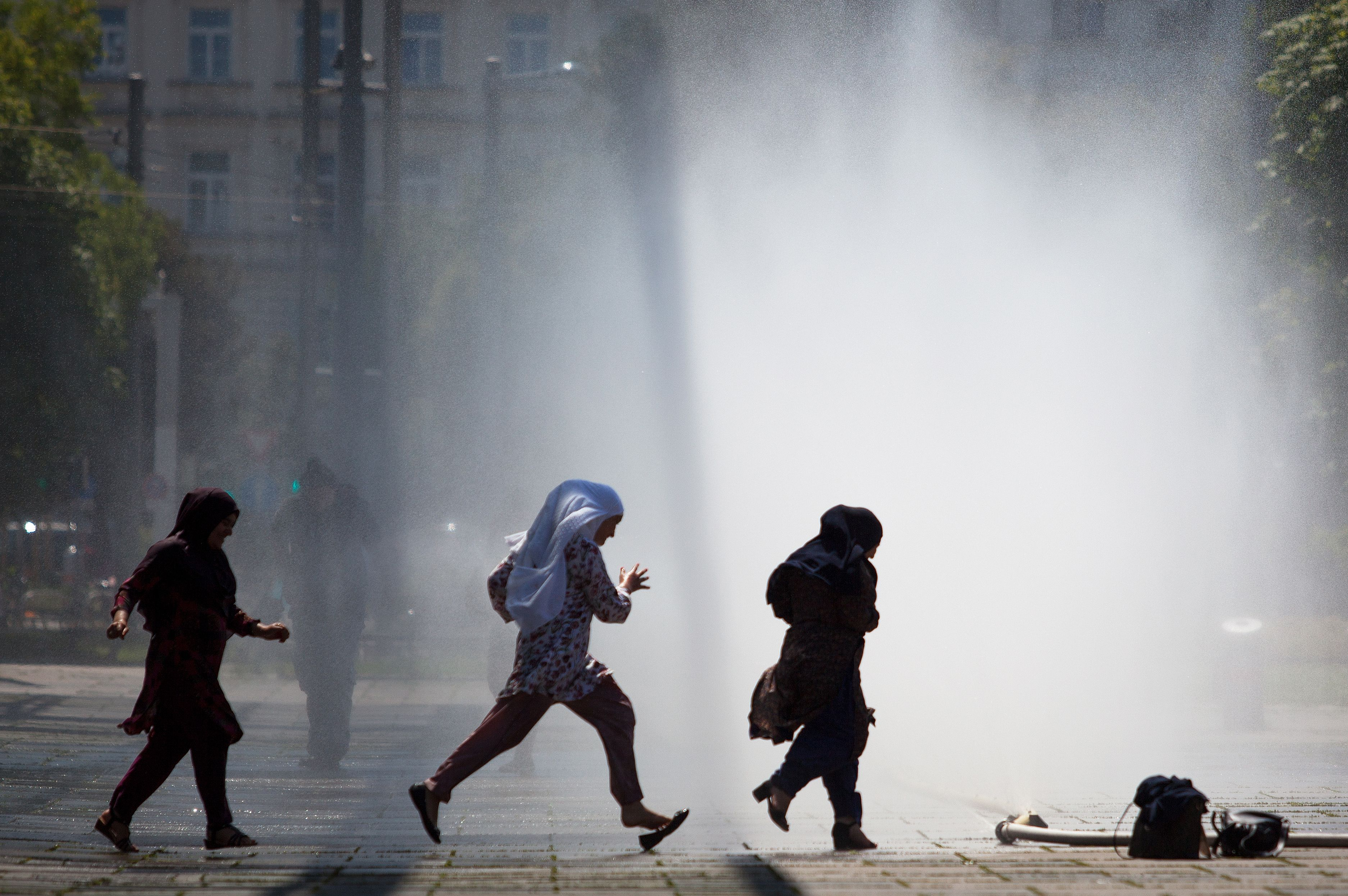 Women run through water sprayed from a pipe at Praterstern Square in Vienna on July 25, 2019.
