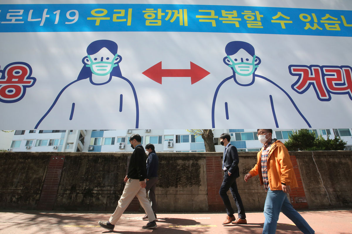 People wearing face masks pass by a banner displaying precautions against the coronavirus on a street in Seoul, South Korea, on Monday, April 5.