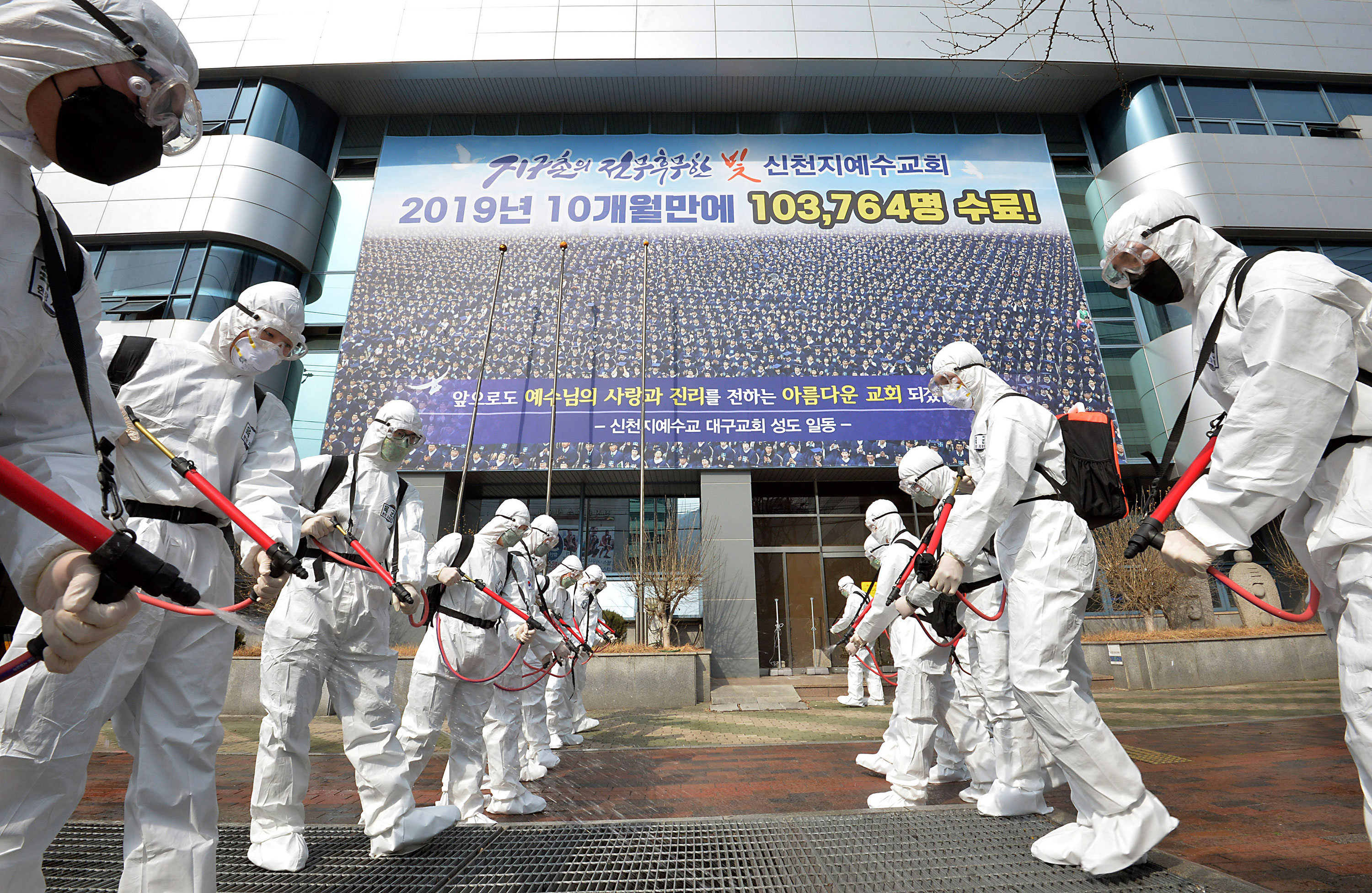 Workers spray disinfectant in front of a branch of the Shincheonji Church of Jesus in Daegu, South Korea, on March 1.