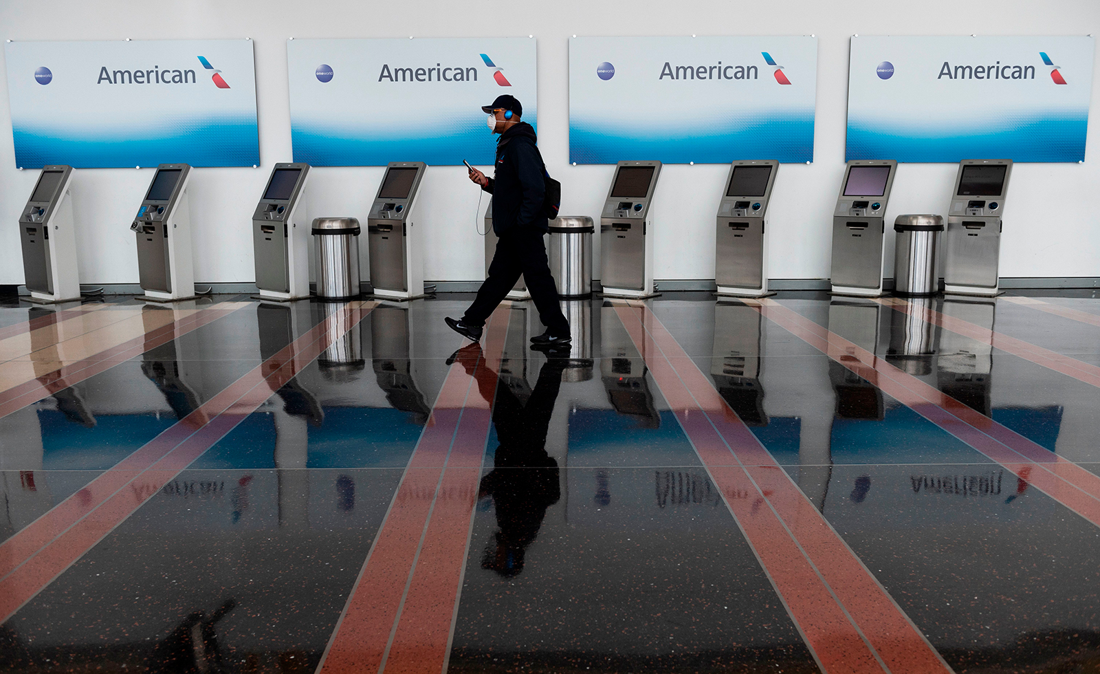 A passenger walks past empty American Airlines check-in terminals at Ronald Reagan Washington National Airport in Arlington, Virginia, on May 12.