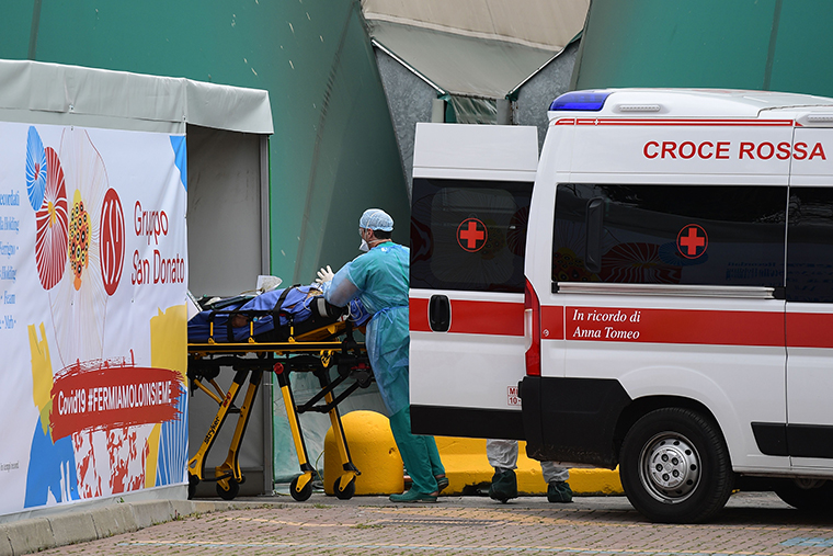 A medical worker moves a patient from an Italian Red Cross ambulance into an intensive care unit set up in a sports center outside the San Raffaele hospital in Milan, in the hard hit Lombardy region of Italy, on Monday, March 23.