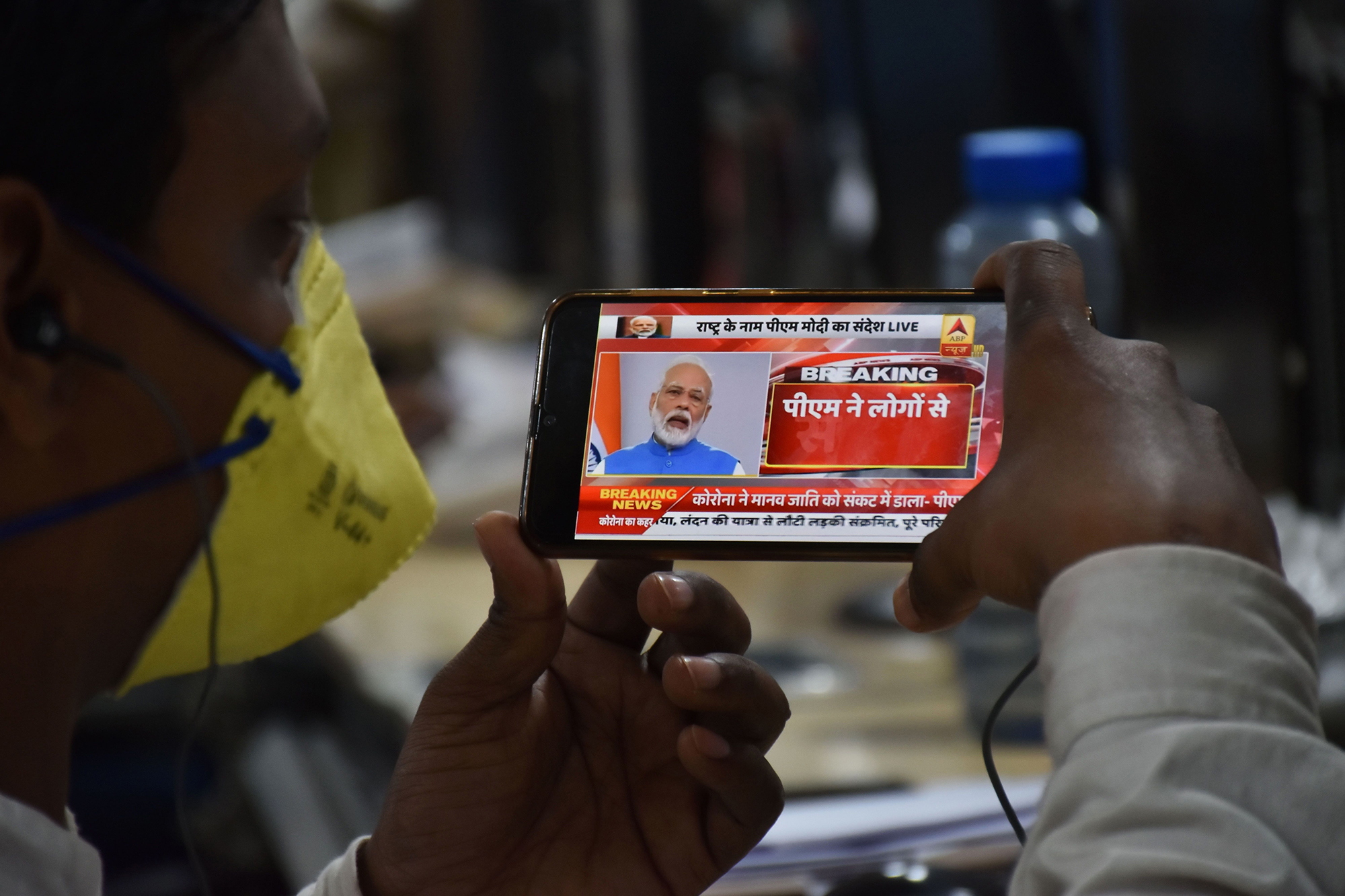 A man wearing a face mask as a preventative measure against the coronovirus listens to Prime Minister Narendra Modi's address to the nation on his mobile phone in Jabalpur on March, 19.