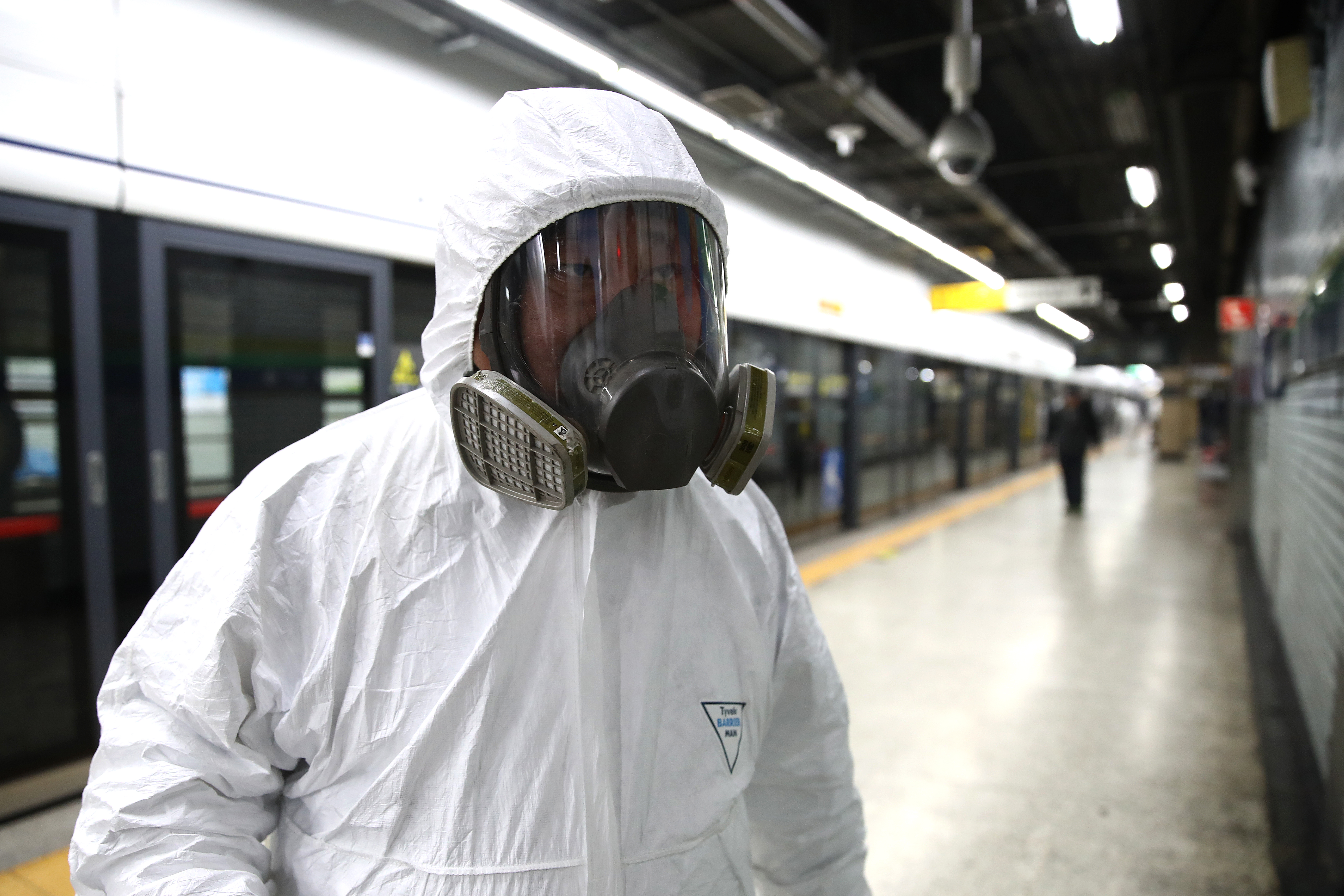 A disinfection worker wears protective gear and prepares to disinfect against the coronavirus at a subway station in Seoul.