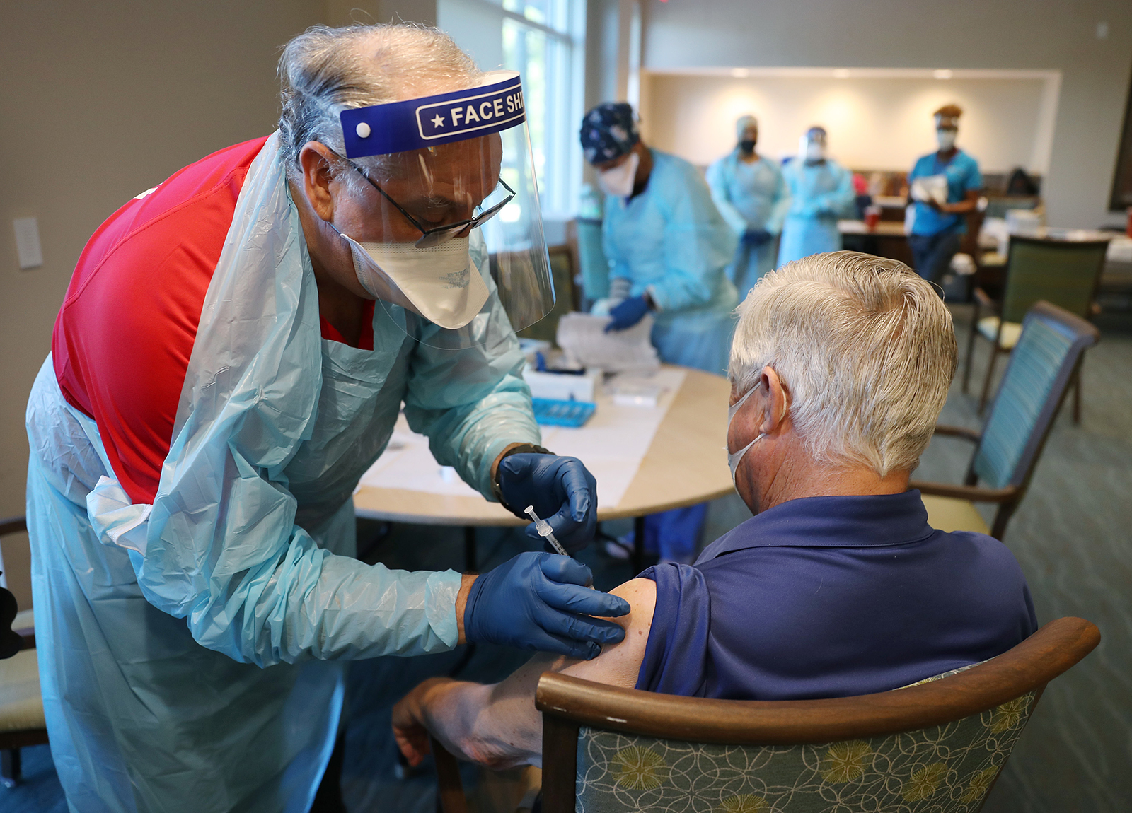 A healthcare worker administers a Pfizer-BioNtech Covid-19 vaccine at the John Knox Village Continuing Care Retirement Community on January 6, in Pompano Beach, Florida.