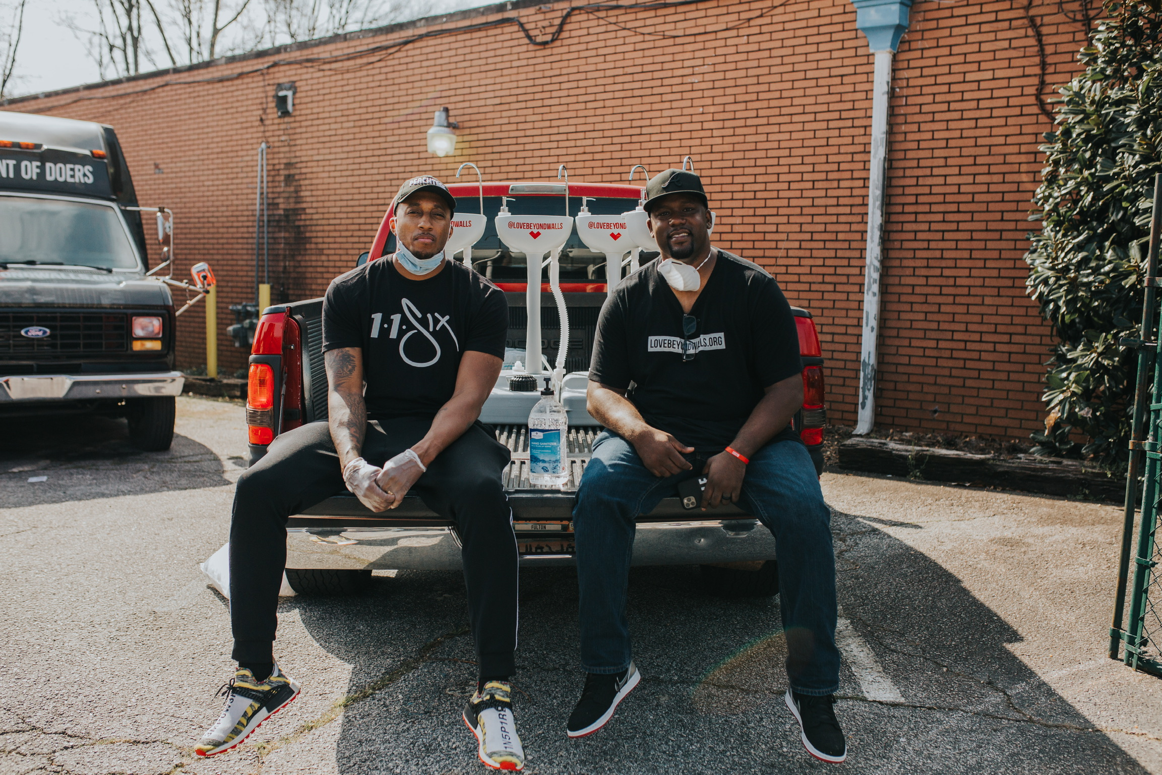 Hip hop artist Lecrae (left) and Love Beyond Walls executive director Terence Lester (right) distribute portable wash stations around Atlanta.