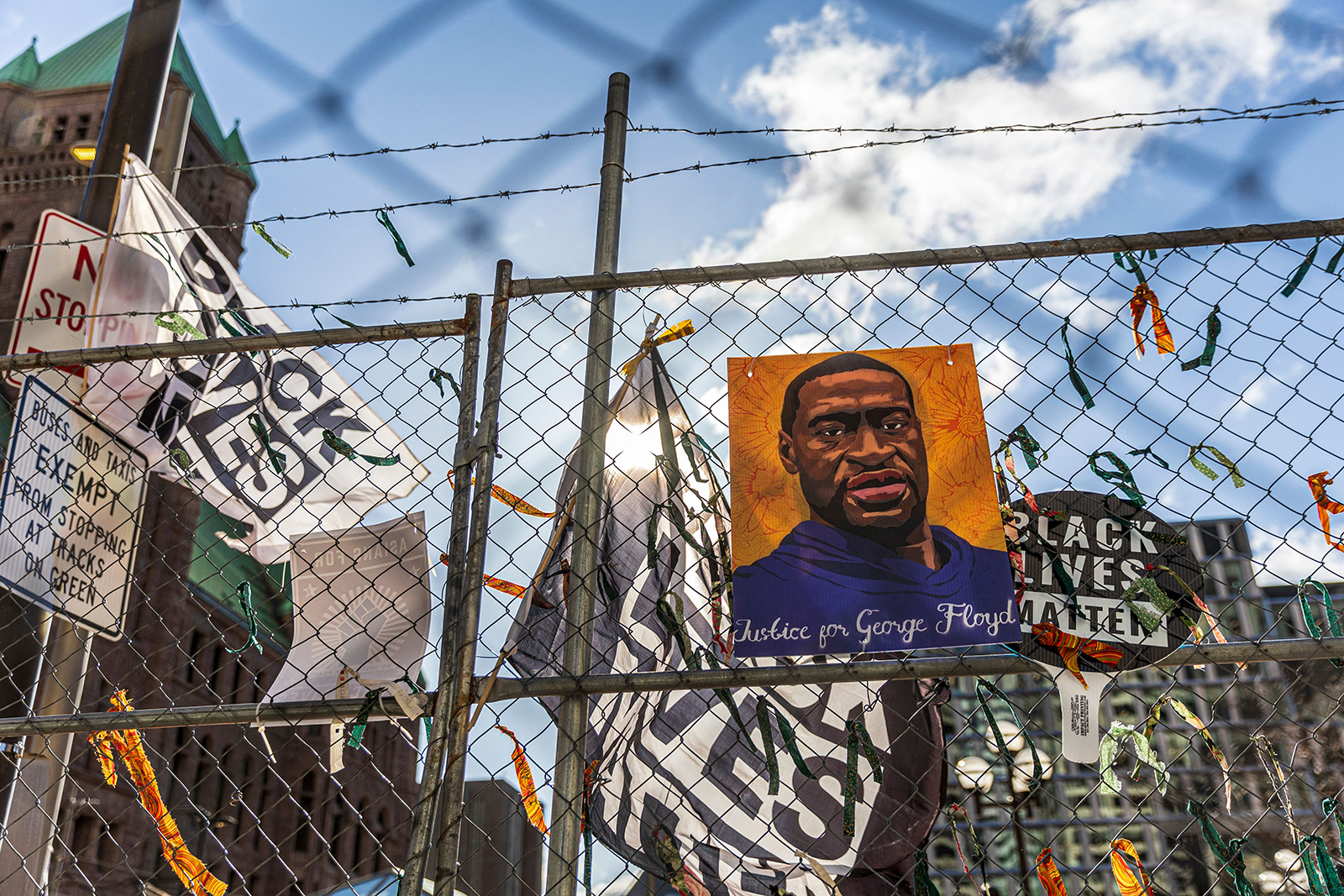 """A poster with George Floyd's picture and a sign reads that """"I Can't Breathe"""" hang from a security fence outside the Hennepin County Government Center on March 31, in Minneapolis."""