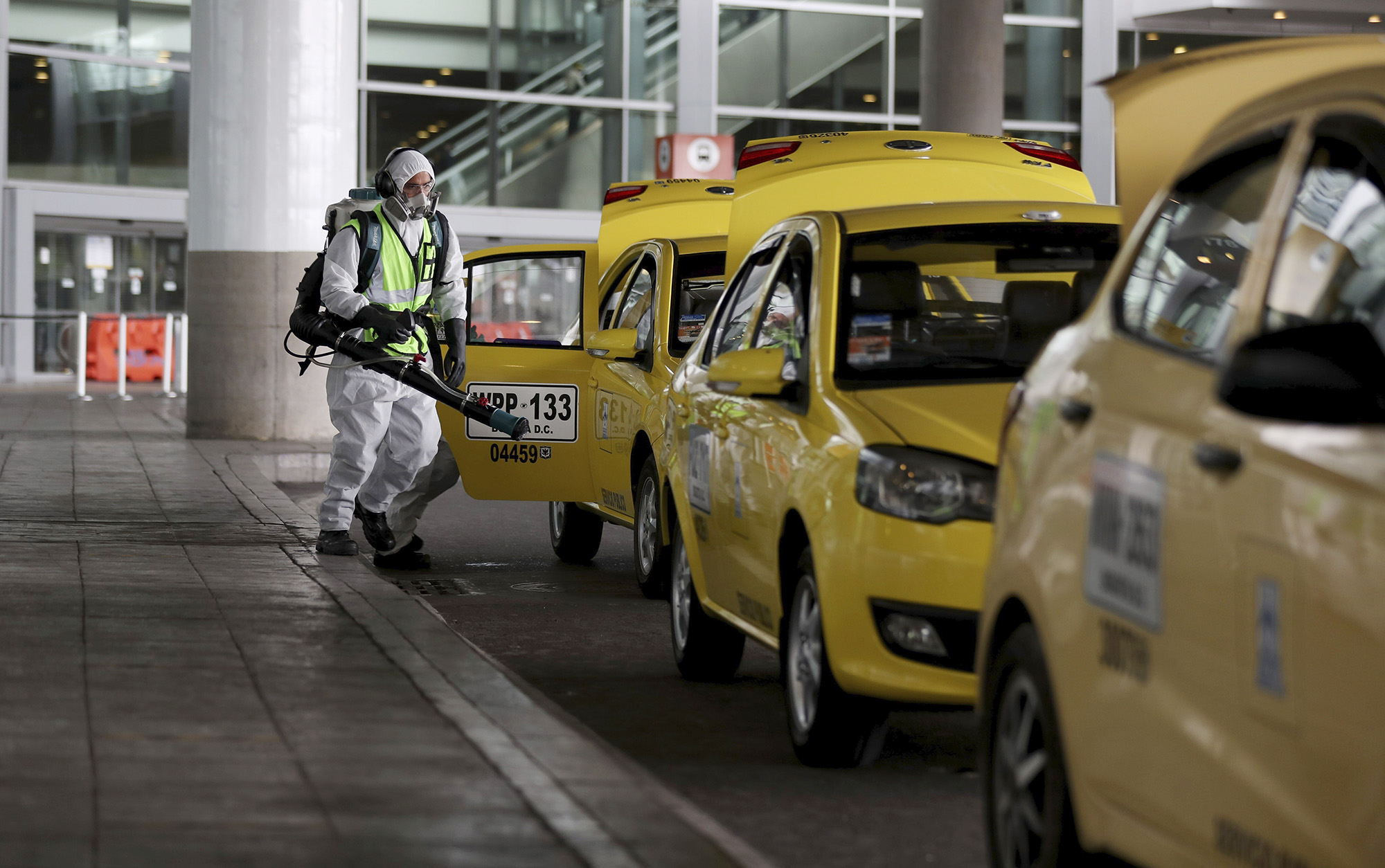 A worker disinfects taxis outside the El Dorado airport in Bogota, Colombia, on June 25.