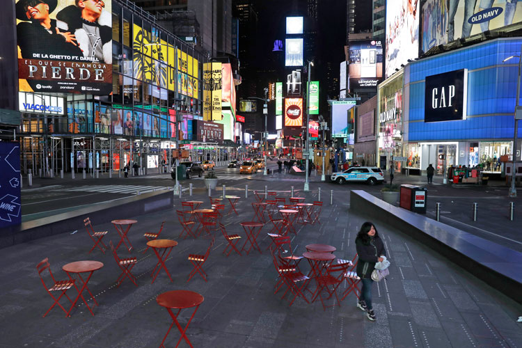 A woman walks through a quiet Times Square in New York on Monday, March 16.