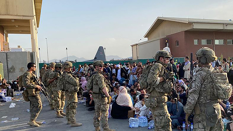 US soldiers stand guard as Afghans wait to board a US military aircraft to leave Afghanistan, at the military airport in Kabul on August 19,  after Taliban's military takeover of Afghanistan.