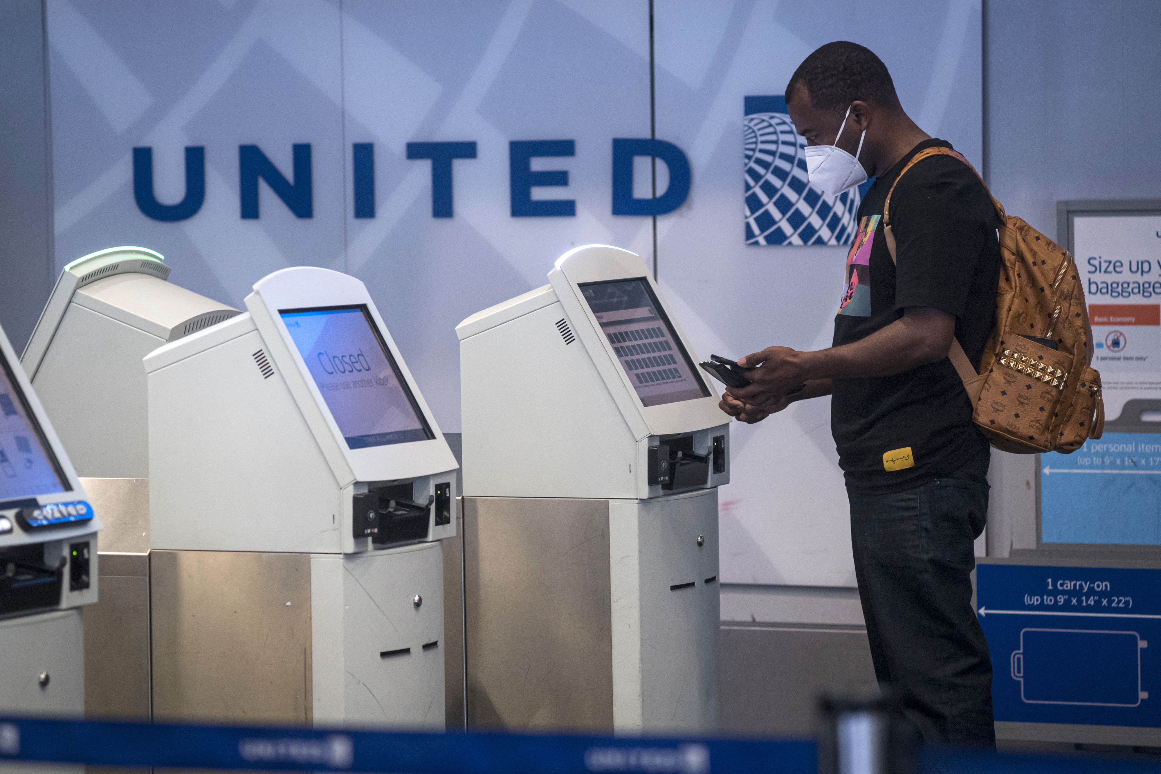 A person at San Francisco International Airport in California uses a kiosk to check-in at a United Airlines counter on July 1.