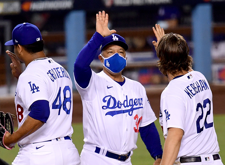 Manager Dave Roberts #30 of the Los Angeles Dodgers celebrate a 3-0 win with Clayton Kershaw #22 and Brusdar Graterol #48, to eliminate the Milwaukee Brewers after game two of the National League Wild Card Series at Dodger Stadium on October 01, 2020 in Los Angeles, California.
